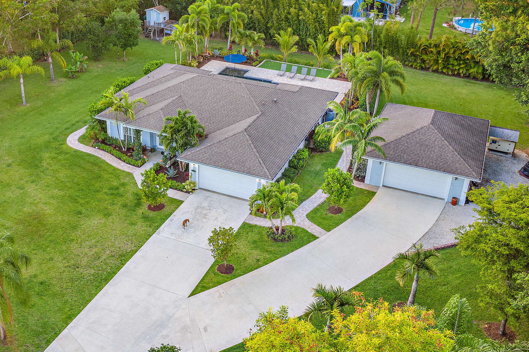 This 4 bed CBS home has it ALL! Built in 2015, it is move-in ready and located on a paved, dead-end street. Its open floor plan has the perfect layout with private office/guest room and split floor plan, cathedral ceilings, plantation shutters, large screened-in lanai and separate 875-sf CBS detached garage (25x35) with epoxy flooring. The 1.15-acre lot is fully fenced with an automatic gate and has an irrigation system. The lush tropical landscaped grounds provide complete privacy, while landscape lighting throughout highlights its features. The oversized, saltwater pool has a heater AND chiller, which you can control via Smart Phone. Surrounded by a large paver pool deck and featuring a putting green nearby. The home also includes a full home Reverse Osmosis System and generator hookup. There are no HOA fees. Bring your chickens, boat, or RV. There is plenty of space for it all!