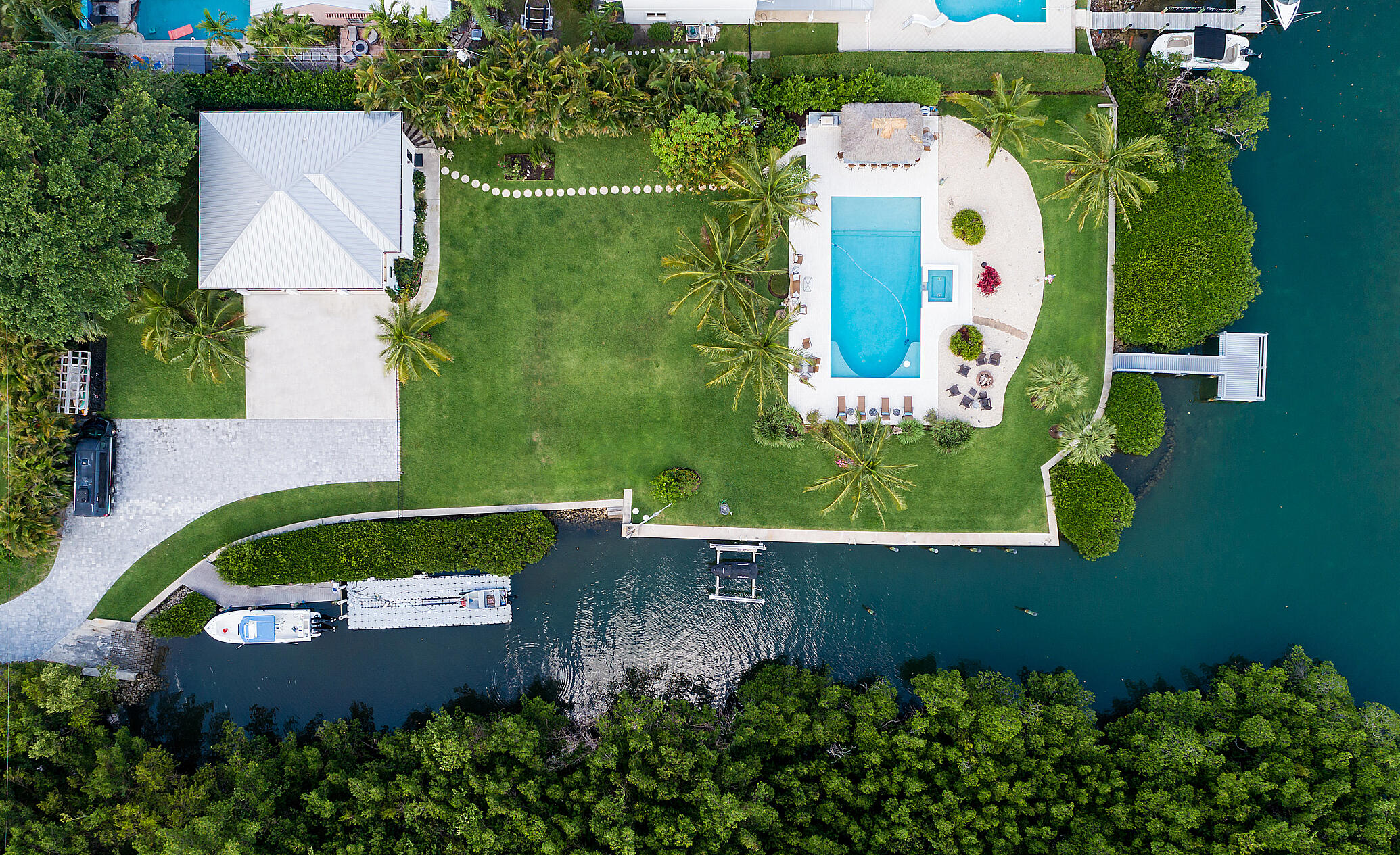 Build your own dream home! This rare waterfront lot, just minutes from the Jupiter inlet, offers expansive blue-water views. This lot, which has 125' of direct river frontage and 225' of canal access, is just under 1 acre. The property includes a 3/2 guest house, private driveway, boat ramp, boat lift, new dock, and newly renovated pool, deck and spa. The high end outdoor kitchen, protected by a tiki hut, includes built-in gas cooktop, grill, smoker and rotisserie, two refrigerators, one beverage refrigerator, double-drawer freezer, ice maker, kegerator, 60-inch flat screen tv and enclosed dry storage. Other features include a fire pit, Sonos surround-sound system for the pool area, gas tiki torches, outdoor shower and Luma outdoor security system. Mature landscaping and mangroves.