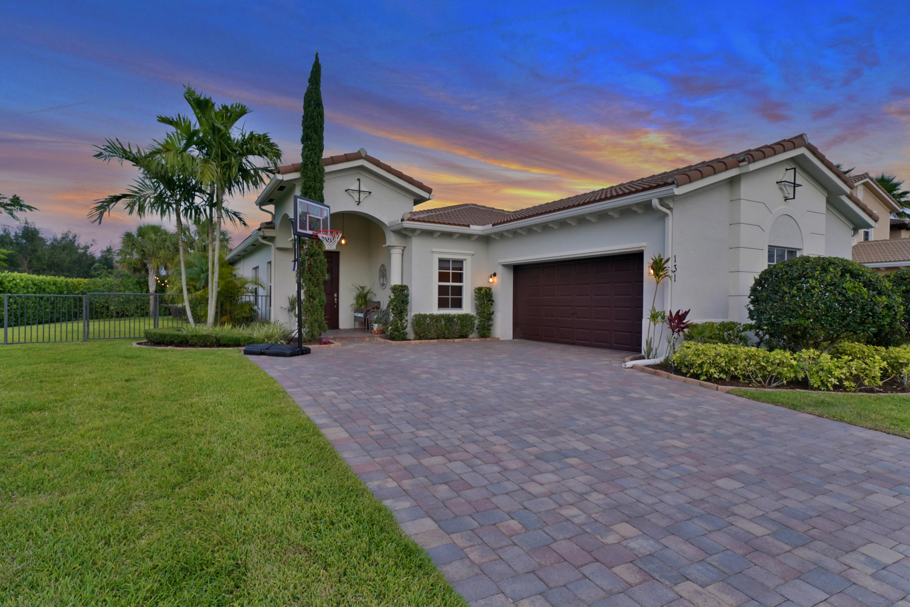 """4 bed, 2.5 bath masterpiece on a LARGE lot 500' from the resort-like amenities of Jupiter's premier gated community, Rialto. Enter and the dining room greets seating 8 adjacent the formal living room, both served by a 1/2 bath. The kitchen stuns with 42'' cabinets, granite counters, glass backsplash, pantry & island overlooking an eat-in kitchen & spacious family room. A covered patio invites you to a fenced backyard paradise while pavers extend the living area w/ a fire pit & an expansive side yard. Inside, the Master Bedroom is a true sanctuary w/ wood-look tile floors, walk-in closet, soaking tub, glass shower & comfort height dual vanity. 3 guest bedrooms with wood look tile floors are served by a full hall bath w/ 2x vanity & glass shower & cabana door. Impact Glass, A-Rated Schools! Presenting a 4 bedroom, 2.5 bathroom Mediterranean masterpiece perched on a massive corner lot over .25 acres, adjacent to one of Rialto's coveted greenspaces and just 500 ft. to the clubhouse and pool. This single-story Giorgio model is the NEWEST home in all of Rialto and has been further enhanced since construction was completed in 2015. From the curb, a turned garage, iron accents and a soaring covered entrance framed by a sole arbor vitae enhance appeal. Enter, and the home's youth is apparent, pristine paint, 20"""" tile on the diagonal and pure silence courtesy of the impact rated glass and doors. A wide foyer opens to the dining room straight ahead, a designated space yet an informal feel. Next, the spacious living room at right, a flexible space takes all the pressure off the rest of the living spaces providing elbow room for the busiest households. Ahead, the kitchen awaits, truly the heart of the home featuring 42"""" shaker style upper cabinets in rich chocolate tones with LED under cabinet lighting, a perfect pairing with the granite counter tops and glass backsplash. An island seats 3 and features a dual sink with Moen fixtures while the kitchen is finished with a stainless"""