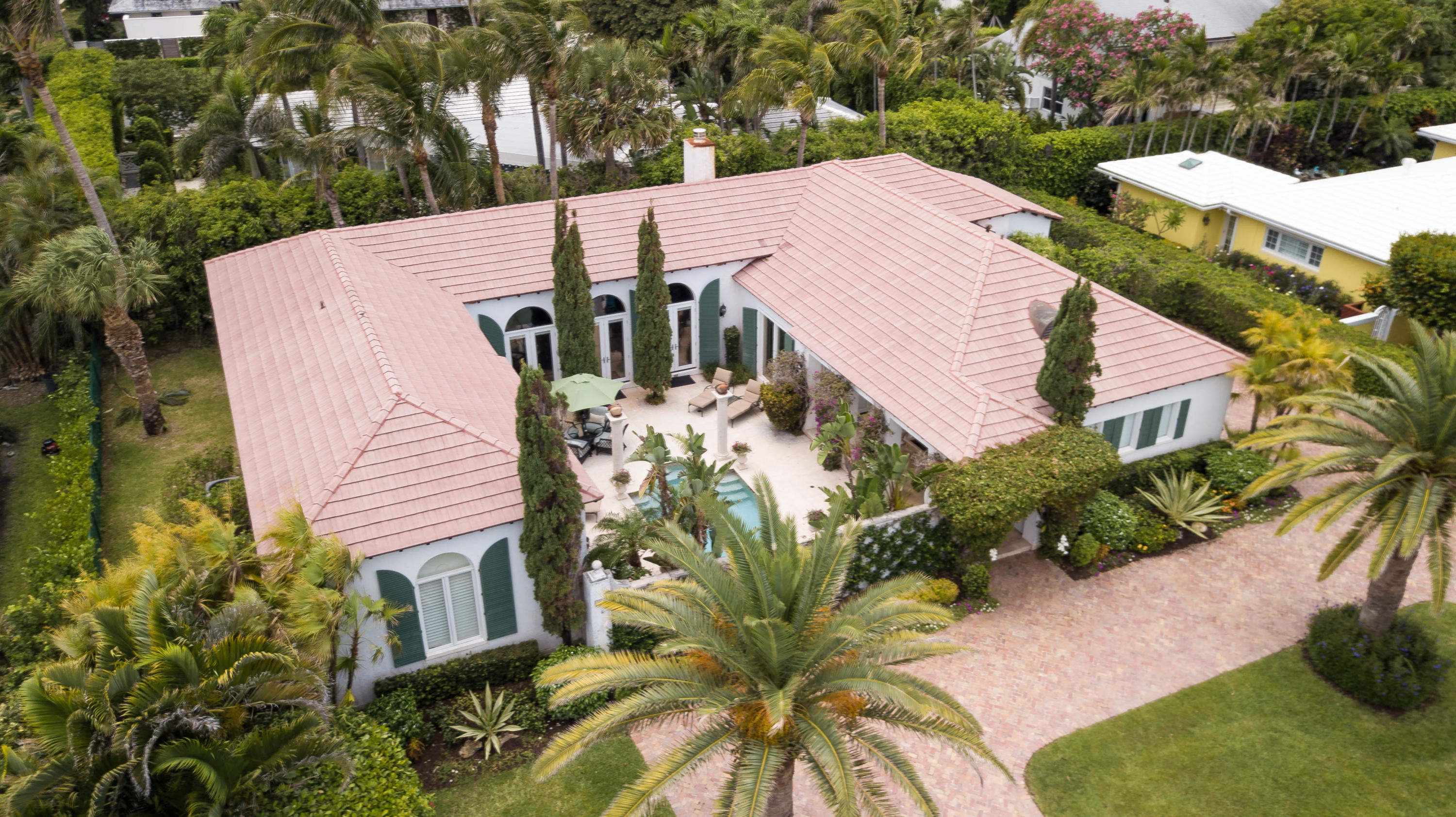 This unique Palm Beach Courtyard home sits on a quiet residential island enclave on the desirable Palm Beach's Southend and boasts 3,146 square feet of interior living space with 3 bedrooms, 3 full baths, 2 car garage and old brick circular drive. Designed by Ballinger Award winning architect, Raphael Saladrigas, the interior features an expansive great room with lofty tray ceilings, beautiful marble floors with Verde S. Denis marble accents in the foyer and fireplace surround. The mantel piece is from the late 1800's. The master en-suite has double walk-in closets and marble appointed bathroom with double sinks. Both the master en-suite and the great room, open to the private courtyard, a tranquil outdoor living area featuring a fountain, heated saltwater pool and a relaxing tropical setting. This property is ideally located within walking distance to Phipps Ocean Park Beach and Raymond Floyd Golf Course.