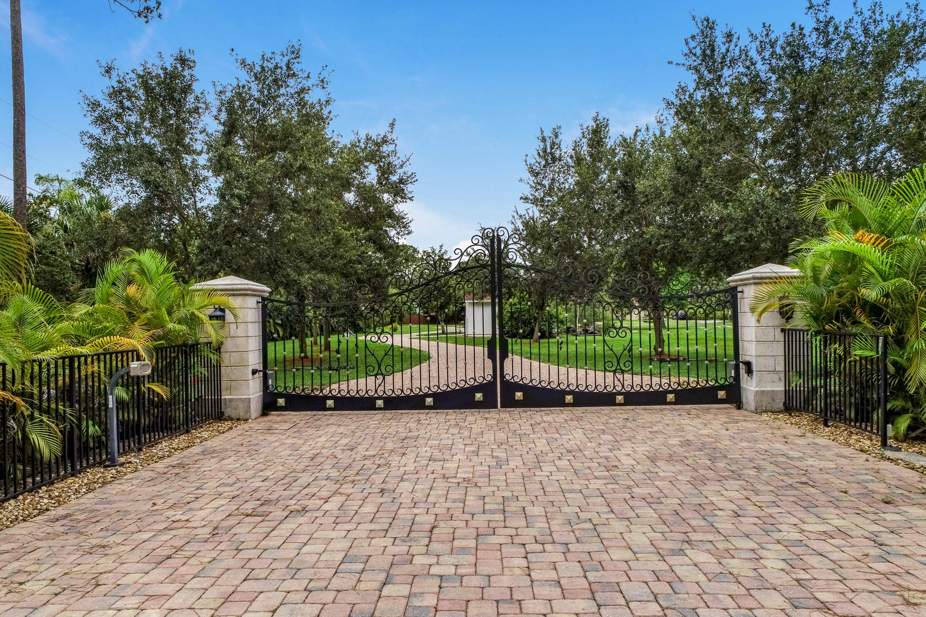This marvelous waterfront property located within a highly desirable area of Jupiter, FL rests on over 100,000 sqft, 2.45 acres of manicured land encircled by alluring fruit trees and 500 Areca palm trees. The double gate offers an S.O.S feature for emergency vehicles and keyless, remote entry for guests and family with camera and cell phone dialing. Experience a quick getaway utilizing the unique resident access road linking to over ten thousand acres of Jonathon Dickinson State Park. This home has an automatic generator powered by five hundred gallons of underground propane tank, backup water system, Tank-less propane water heater. The interior of this two-floor gem provides residents with seven bedrooms, six bathrooms, which does include a ground floor master suite with a large marble bathroom and deck; spacious chef kitchen with stainless steel appliances; gas stove range and electric oven; a large island with seating up to six; elegant Marble and Wood flooring; plantation shutters, and high impact windows. All windows, doors are with an analog monitored alarm with powered backup.  Conveniently nestled within the property exterior for relaxation and outdoor entertainment is a commodious patio; heated outdoor pool, jacuzzi with full cabana shower; 11K boat lift, a floating wave runner dock attached to NW Loxahatchee River. Ten minutes to the beach via car or to the inlet by boat and less than three hours to Bahamas (depending on hp). This home also provides the highest underground Internet cable of one Gigabyte of download speed.
