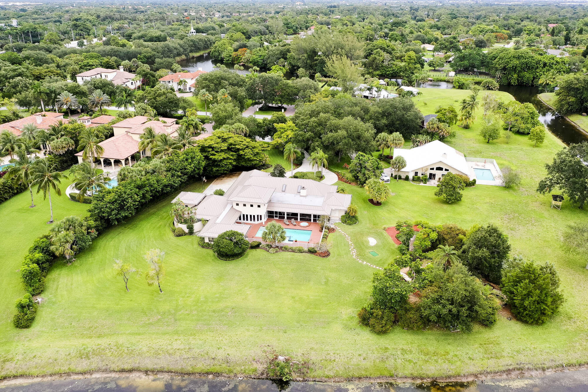 One of most desired locations in Steeplechase. Close to the North gate, away from any street noise. Private Cul de Sac Waterfront Lot. 1.25 acres - Pie shaped with 280' of gorgeous landscaped water frontage. Spacious rooms featuring En-Suite baths for each Bedroom. Large covered Porch/Lanai overlooking the enormous pool with waterfall and separate hot tub. The patio also includes a fully equipped Summer Kitchen.  Private guest suite detached from the home.  Putting green, custom running stream oasis with sitting areas looking out on the enormous back yard and water views. Huge potential to make this your Dream house!