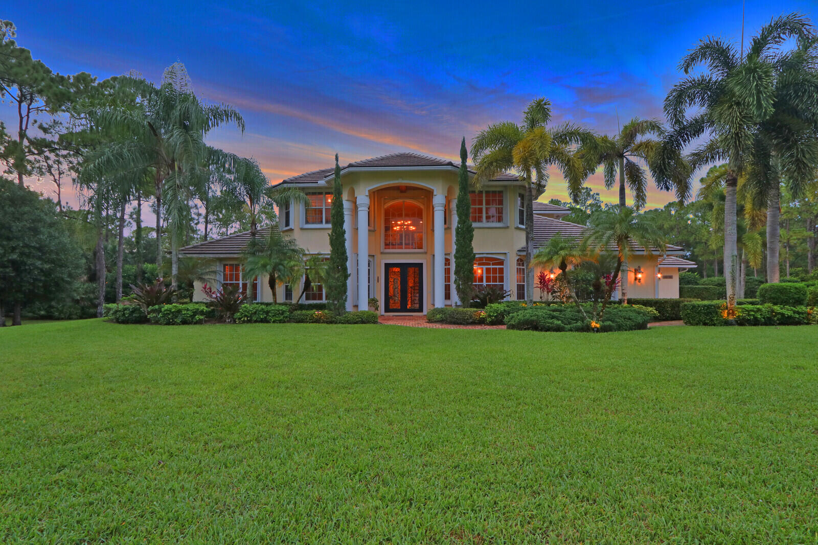 Step into the private oasis in the most desirable area of Jupiter Farms. This is a true, one of a kind estate home on a lush landscaped 2.5 acre beautiful property . This home is not only perfect for entertaining, working from home, raising a family but also as a private wellness retreat for the most meticulous buyers looking for luxury, privacy and high-end finishes. This home has 5br/4ba/2 offices/yoga studio/3 car gar. home with over 6300 total sq.ft. The double gated front entrance with Chicago brick driveway is just a hint of the magnificence inside, from the two-story well-lit foyer that opens straight through to the living room, formal dining room and spacious family room that welcomes you with decorative Chicago brick accents, wood burning fireplace & built-in wall unit, Brazilian cherry floors and a study on the left side of the home. Friends & family will love to gather around the well-appointed kitchen, that includes granite counter tops, custom wood cabinetry, a large center gas cook island, desk area, butler's pantry, and an additional dining area with access to a covered lanai that includes a summer kitchen, a gorgeous pool/jacuzzi with rock water fall feature, tiki hut, fire pits & night lighting. The first-floor secluded master suite is in its own wing, it is complete with French doors to the lanai, decorative ceiling, dual walk-in closets, and a luxurious spa-like bathroom with a two-person marble tiled shower, separate tub & double sinks with ample storage. Also, on the first floor a guest suite & cabana bathroom is on the other side of the home that could be used as a mother-in-law or maid quarters. The gorgeous staircase leads to the 2nd floor with three additional bedrooms, 2 full bathrooms one of which is a jack & jill bathroom, a study/office and a yoga/workout studio with a private sauna. A must see!