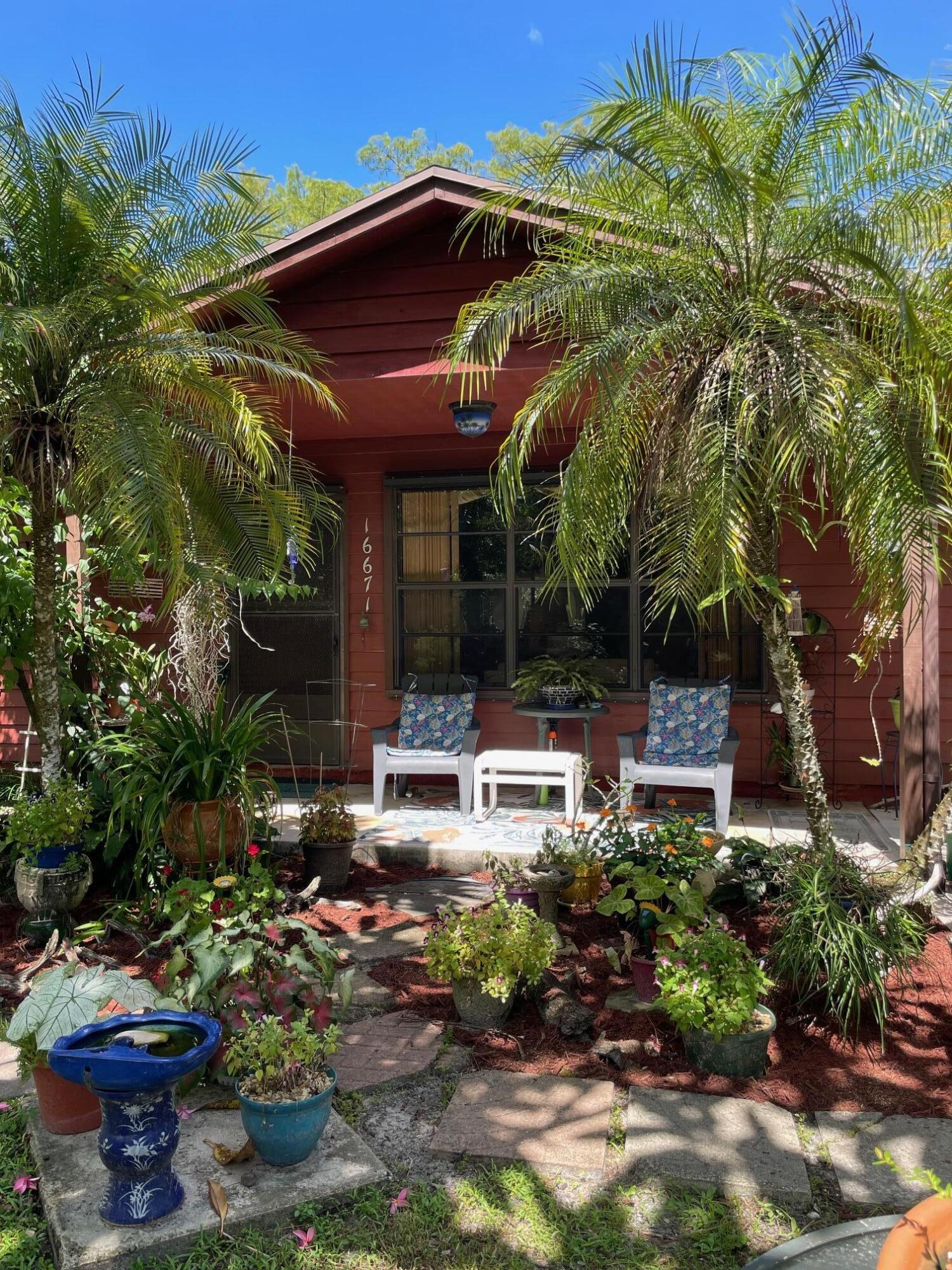 This charming one-story home, at the end of a winding road, nestled in amongst tropical landscaping and flowering trees, is your next home!  The fire pit welcomes you to join in conversation as you take in the beauty of the day. The current owner is an artist, who enjoys the screened patio for natural light and inspiration, overlooking the pond. High ceilings in the living area stretch the feeling of space. This 3 bedroom, 2 bath, 2 car garage, dining room, living room, all in a great area of Jupiter Farms. A/C and Water Heater (2019), Roof (2005). 1.25 acres...Come and feel nature, inside and out!!