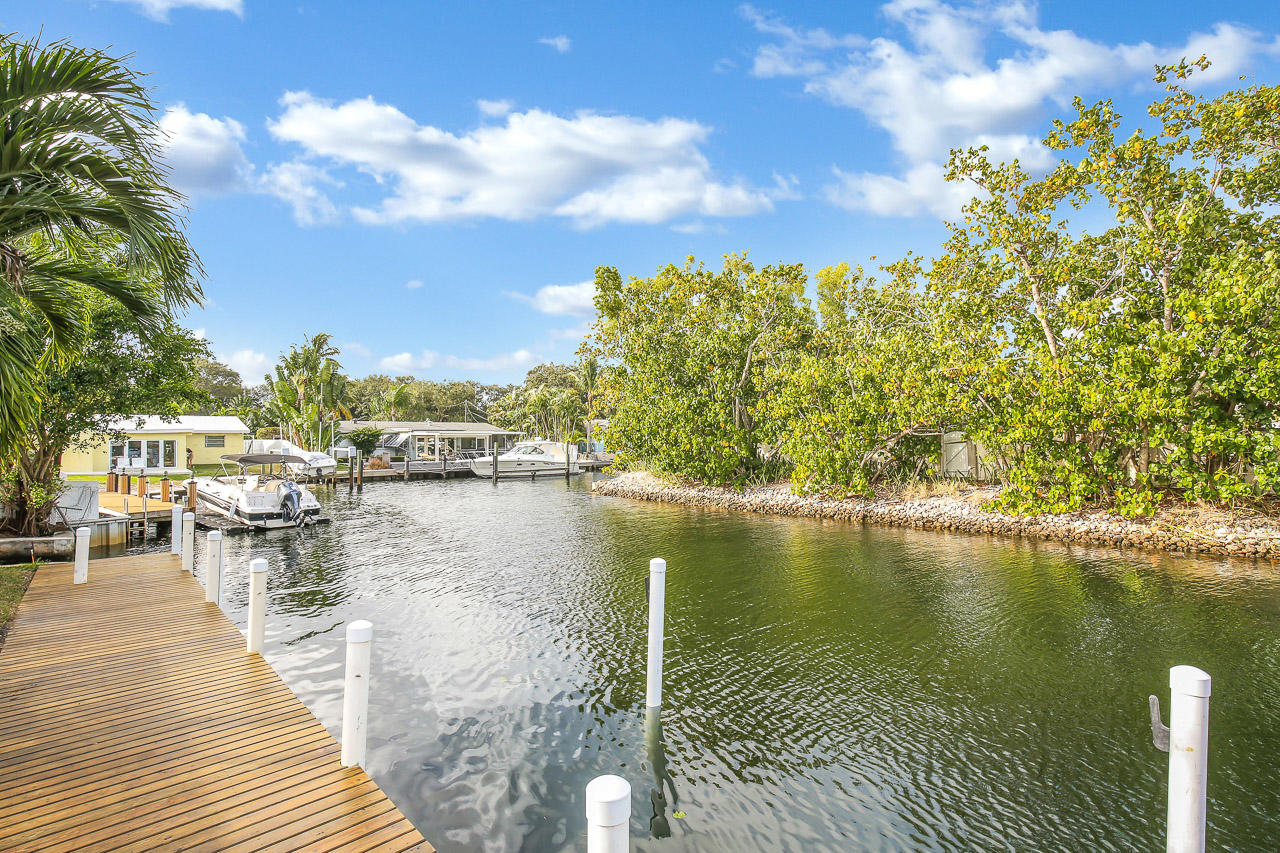 BRING YOUR BOAT UP TO 80 FEET! This direct waterfront home in Pirates Cove has a dock that will accommodate an 80' boat, (no fixed bridges), private water views, gorgeous white porcelain tile throughout the living area, kitchen w/ updated cabinets, 3 bedrooms or 2 bedrooms and large media room, screened in salt water pool, patio gazebo, wood deck, cabana bath, 1 car garage, fenced yard, pet friendly. This home is 4 lots off the Intracoastal and is in a multi-million dollar neighborhood. Great location! Close to restaurants and shops on PGA and in the heart of Palm Beach Gardens. Landscaping and pool maintenance included in rent. Don't miss out on this rare waterfront home! $500 /mo for dock usage. Virtual tours available.