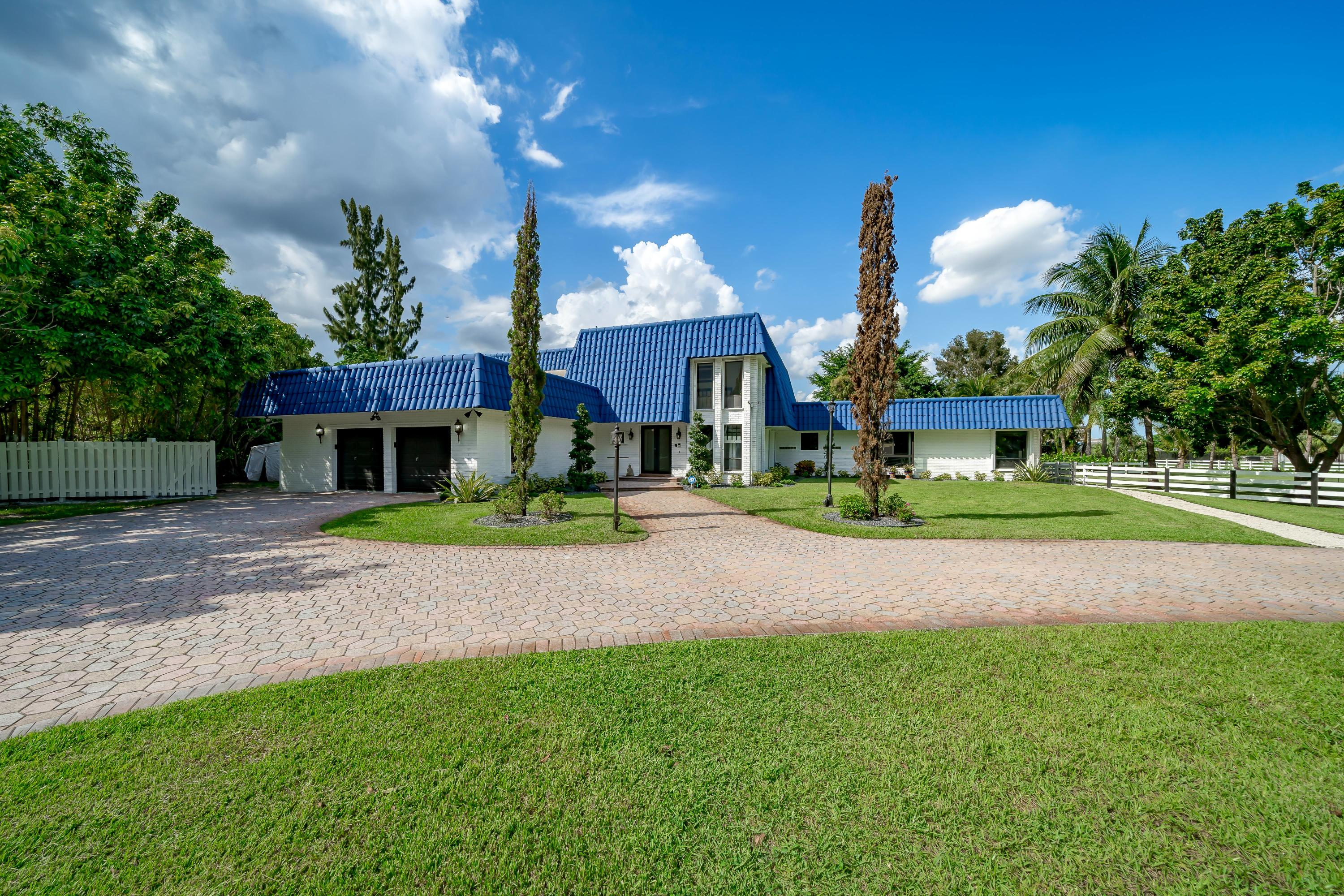 Privacy galore in this multi-generational estate designed with total functionality. Located on a quiet street and surrounded by beautiful trees, this home sits on 0.84 acres! Completely fenced, with a circular driveway and a 2 car garage. Enjoy South Florida living at its finest with a massive pool deck offering plenty of deck space & grass for hours of outdoor fun. This spacious area creates the perfect ambiance to enjoy ''Alfresco Dining'' while taking in the beautiful sunsets.  The summer kitchen even offers a pizza oven for family gatherings full of fun.  The sunken built in fire pit is a perfect way to wind down after a hard days work.  The floor plan offers an ideal layout with an oversized Owner's Suite downstairs as well as another full bedroom and bath. The second story offers 3 spacious bedrooms and 2 full baths. One bedroom has its own balcony where you can bask in the sun or use as a private retreat. The light and bright gourmet kitchen is every Chef's dream.  Boasting two hood vents, stove top, hibachi grill, wall oven, and plenty of custom cabinets.  The Live Edge Countertop will be the talk of every gathering! Adjacent to the Kitchen is a custom Wine Bar/Serving Area.  Perfect for large parties.   The large living area offers a wood burning fireplace and French doors leading out to the pool deck.  New flooring has been added to the entire first floor and upstairs hallway.  3 commercial grade a/c units, 2 water heaters, new baseboard throughout, new light fixtures throughout, new, new, new. This move-in ready estate is freshly painted inside and out creating an open canvas with its neutral décor.  NO HOA fees offer the freedom of having the space you need for RVs, Trucks, and other cool toys.    See complete list of upgrades attached in the MLS.