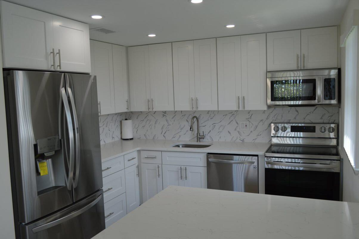 A gorgeous, completely renovated spacious 2 bedroom, 2 baths much sought after corner unit in the gated community of Century Village, in the heart of West Palm Beach. Kitchen features all brand new brand stainless steel LG brand appliances including dishwasher, microwave, refrigerator, and stove. There's also new modern white soft close cabinetry, counters, stainless sink and faucet and a new ceramic backsplash. Both bathrooms are completely renovated in a modern design.   Throughout the home there is brand new flooring, doors, modern luxury lighting, fans and fixtures, upgraded baseboard molding, freshly painted and central air conditioning. New sliding doors provide direct access to the enclosed patio from both bedrooms.