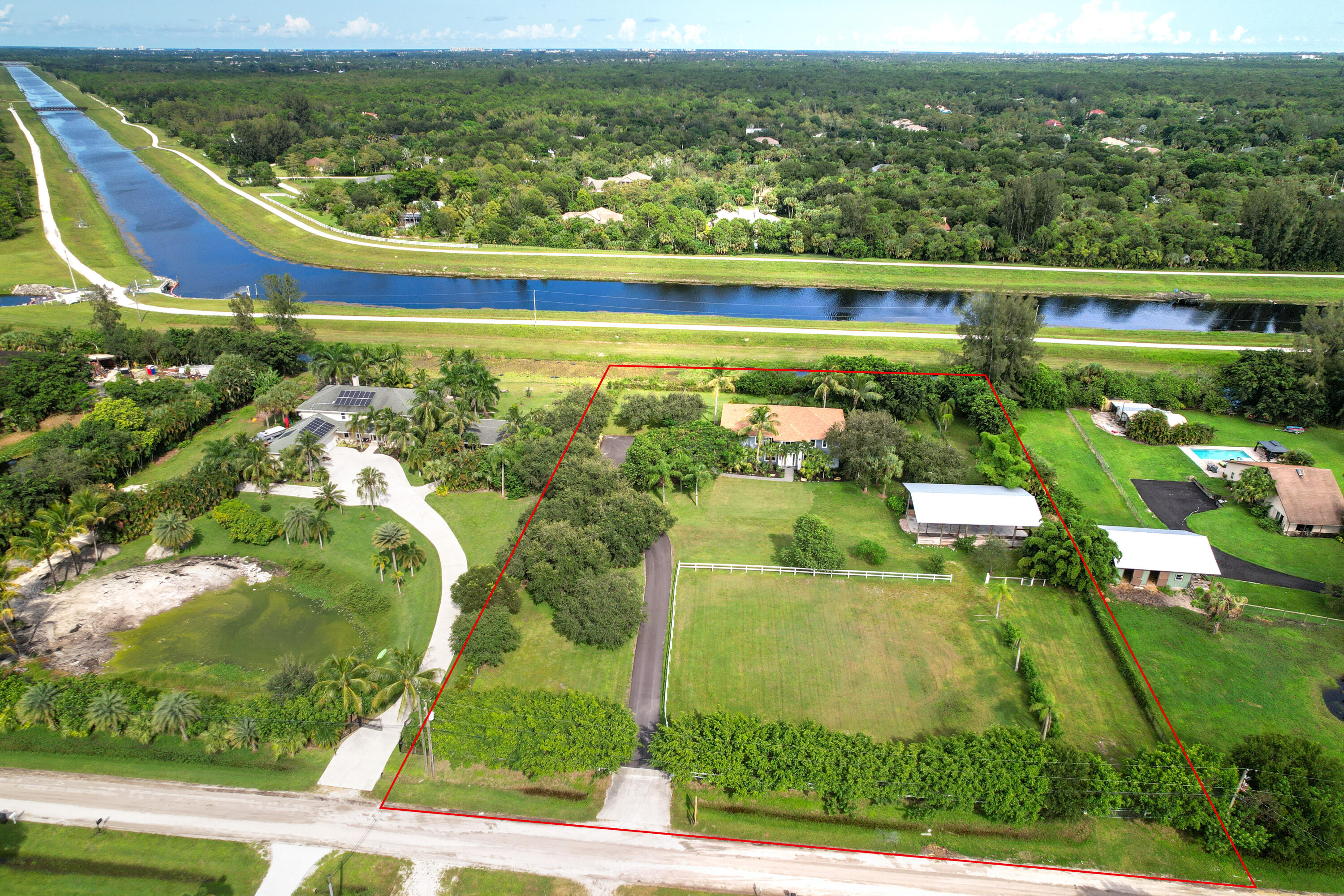 Best price per/SF over 3000SF! Savor the solitude on the eastern edge Jupiter Farms minutes to world class beaches & dining. Enjoy breath-taking sunrise vistas over water from the second floor kitchen/great-room in an enclave of 3000-5000SF homes.  Nestled on nearly 3 acres of mature landscaping & a tree-lined driveway, RanchVista invites you to own a premium piece of paradise in Jupiter. The oversized pole barn provides endless opportunities for equestrian, storage, or business uses while the 4 car garage increases the appeal for those with toys or business needs. From the roof to the appliances, the infrastructure of this home is prepared for years of maintenance-free living. Enjoy this home as presented, or creatively tailor the 4360SF this rarity offers.Inside pics virtually staged.