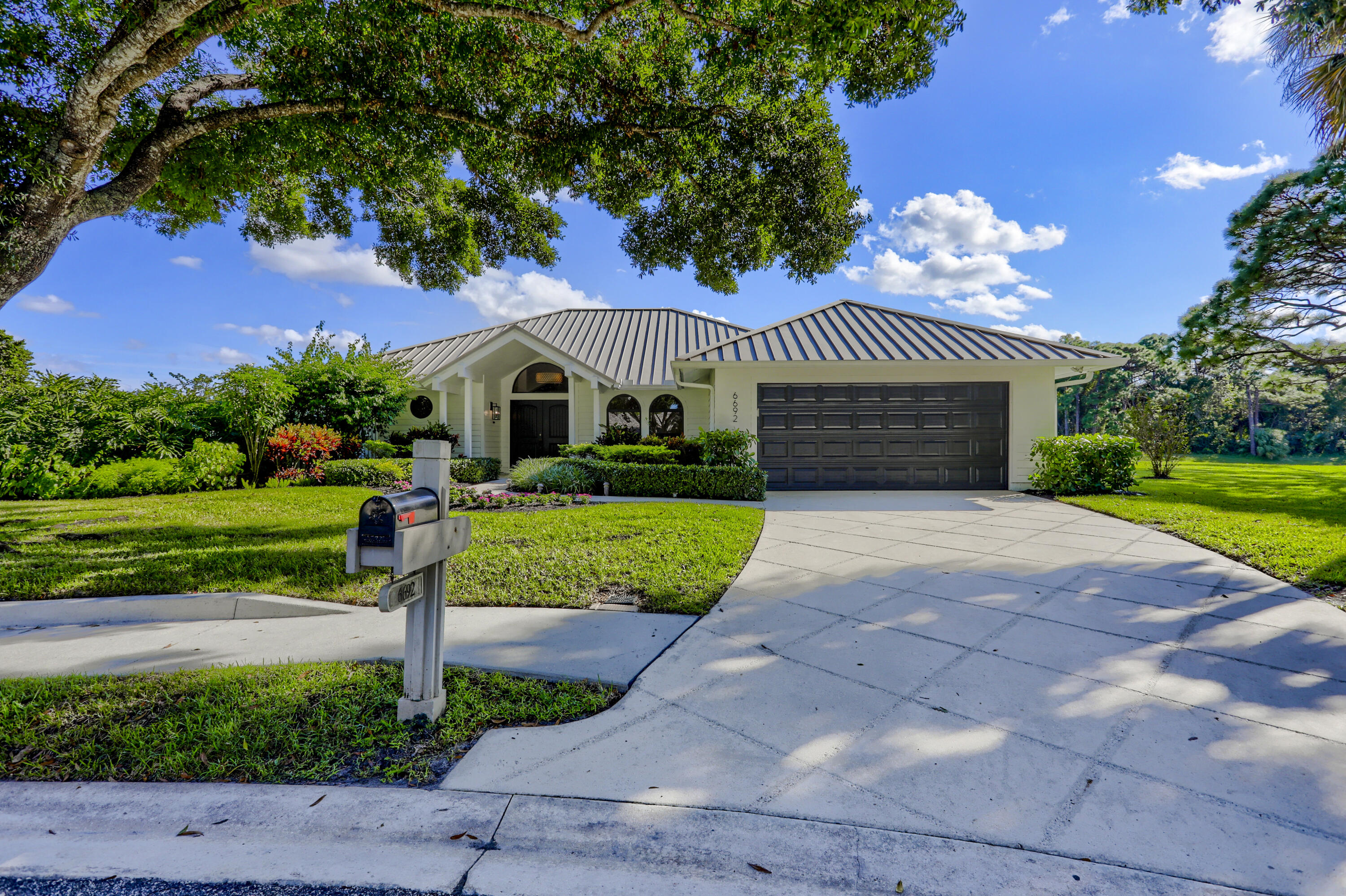 Meticulously maintained! Charming home situated on an oversize cul-de-sac lot, showcasing 3 bedroom 2 bath split floor plan, dark wood floors throughout, custom closets, walk in pantry, stainless steel appliances, hurricane impact windows & sliding glass doors, metal roof, AC replaced 2020, newer hot water heater, plantation shutters, screened lanai & heated pool with private panoramic lake views, lush landscaping, & much more. The owner thought of everything!