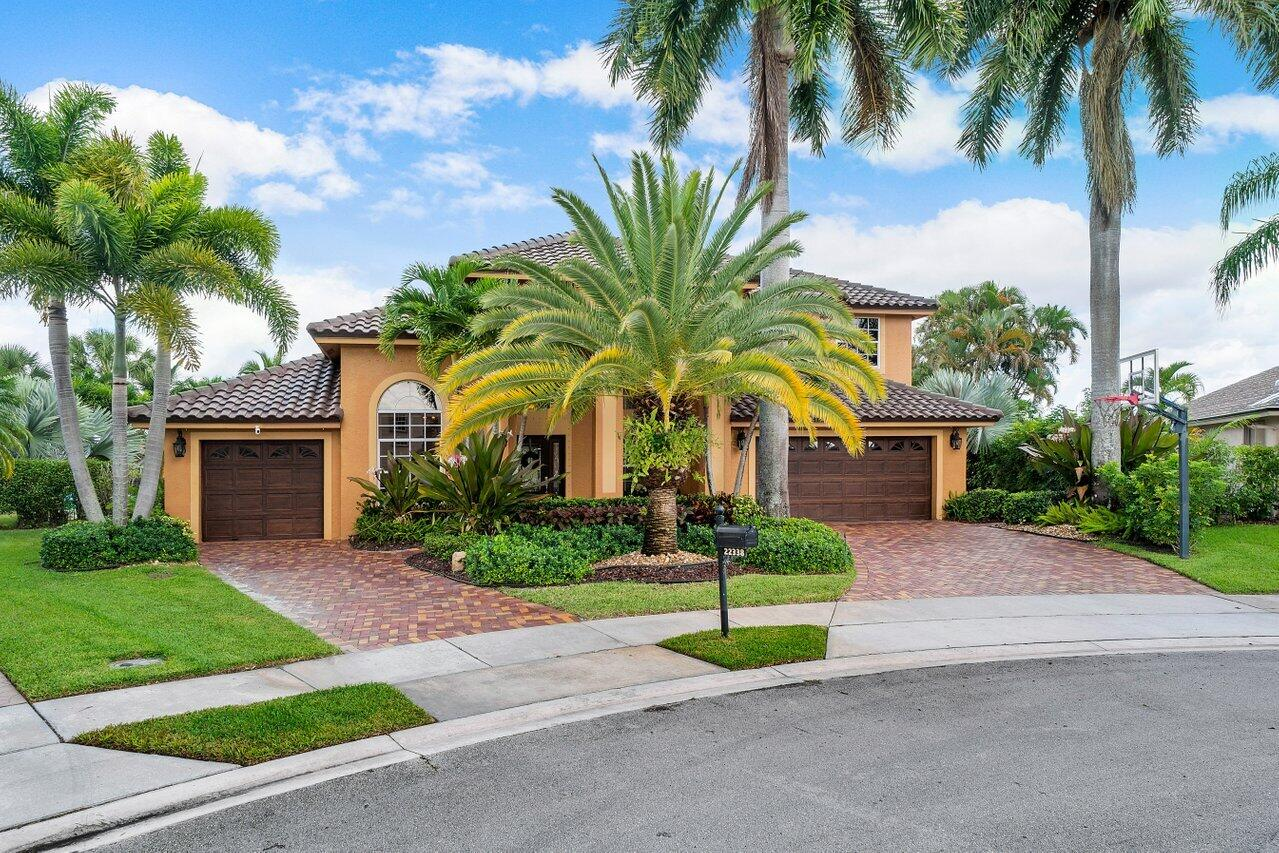 """Once in a lifetime opportunity to own the CROWN JEWEL of Boca Winds, tucked away on a breathtaking waterfront cul-de-sac lot with north/south exposure in the community's prestigious Carlyle Estates subdivision. This trophy property has been masterfully reimagined inside and out by the current owners of 20+ years, and is now available in immaculate move-in condition with a BRAND NEW 2021 tile roof! Relish in escaping to a resort-like setting, felt immediately upon arrival, with eye-catching curb appeal highlighted by brick driveways and perfectly manicured landscaping. Soaring high ceilings and a dramatic two-story entrance with sparkling water views are sure to impress once inside, as natural light pours into and across 3,624 Living SqFt. (See Supplement Remarks for FULL LIST of upgrades). This """"Essex II"""" estate floor-plan boasts a noteworthy first-floor guest ensuite, powder room, and an expansive first-floor primary suite with striking pool and lake views. Upstairs are three additional guest bedrooms, a bathroom, and an accommodating oversized loft featuring even more impressive panoramic lake views! Every detail of each upgrade was scrutinized and meticulously executed, enhancing this show-stopping estate to a caliber that remains completely unrivaled.   Exterior Improvements: - Brand new barrel tile roof completed September 2021 with 90lb underlayment upgrade. - Multi-color clay brick paver driveway w/wrap around side walkways. - Heated pool and hot tub w/remote control and color changing light.   - Expanded 12x12x1"""" travertine patio and tumble marble marble pool remodel. - River Rok natural pebble pool finish. - Large outdoor rear patio awning and enclosed covered screen room. - Cabana bathroom with travertine marble. - Aluminum hurricane shutters all windows and doors. - Automatic outdoor insect misting system w/remote control. - Custom faux painted exterior garage doors w/security keypad. - Custom design landscape. - Dual AC systems.  Interior Improvements: -"""