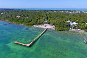 Oceanfront Estate with Deep Water Dockage. Rare opportunity to own or redevelop! One of the few private estate parcels in Islamorada with 400+ ft. of waterfront on 4.3 acres of upland and some of the deepest oceanfront dockage in the Keys. Winding driveway leads through tropical gardens to the 1934 settler's beach home which is now an updated 3/3 with relaxing Old Florida feel & open ocean views. Zoning allows for weekly vacation rentals. Truly private with no neighbors in sight until the end of the dock. You must experience this property to appreciate the hush of the palms and the historic, peaceful old island magic. Call to arrange a private showing.