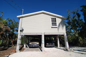 Tropical Paradise in Grassy Key, Three Bedroom-One Bath Home located on a Private Fenced Lot in a Quaint Neighborhood. Brand New Metal Roof. Large Covered Carport under the home for Parking or additional Storage. Plenty of Parking Space for an RV, Boats, Trailers, Jet Skis. Public Boat Ramp a convenient 5 Minute Drive. Marina close by offering sub $200 per Month Wet Slips. NO HOA! LOW TAXES!