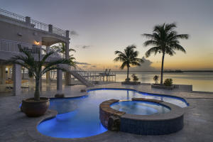 Be entranced by spectacular open water views from this rare find on the bay side of quiet Big Pine Key.  Boasting nearly 4,700 square feet of high-end construction in 2014, this home offers attention to detail in its generously proportioned rooms, multiple porches, roof top decks and resort-style pool with water feature, spa, chiller and heater.  Five parcels comprise over an acre of land, while two 15,000# boat lifts present docking options at the end of the 75' open water pier or on the 140' of protected canal-front with concrete seawall, boat ramp and cut-in boat slip on the property across the street. Key features include the standby whole-house propane generator with 1,000-gallon underground propane tank, elevator to all three levels, surround sound throughout with independent