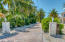 Enter the property along a lushly landscaped driveway