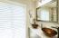 The first floor master bathroom has twin vanities and custom shades.