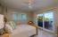 This guest bedroom has sliding glass doors that open to the oceanfront veranda