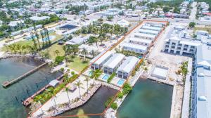 Strong Investment Opportunity! Private turn-key  waterfront compound w/ minimal expenses for weekly rental community. Eight 4 bedroom 3 bathroom new homes built to windstorm standards. Each home is setup to enjoy their own privacy w/ balconies, covered parking, dockage & private pools. Excellent rental history & future bookings perfectly setup to maximize rentals & minimize expenses. Zoned Mixed Use Commercial with 1.38 acres and features commercial property directly on US Hwy-1with redevelopment opportunity on the close to ~13,000sf  lot. Located next door to the Courtyard by Marriott in Marathon, FL at mile marker 48.2 in the Florida Keys.