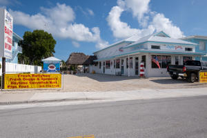 Unique chance to own improved waterfront commercial property in Islamorada, Florida. All concrete block building completed in 2016, comprised of four (4) separately metered units. Sixty eight (68) feet of waterfront, with four (4) dock slips. Tiki hut and free standing ADA compliant concrete block restroom. Three units of approximately 1200 sf presently occupied by tenant outfitted for retail space. Fourth unit finished as 1/1 efficiency studio perfect for monthly rental, and eligible for vacation rental; allowing for multiple sources of income. Located on Old Highway with clear visibility from overseas highway in high traffic area. Zoned VC, allowing for office, retail, boat rental and sales, and more. Flood panels for all doors.. Floor drains throughout. EXISTING BUSINESS NOT FOR SALE.