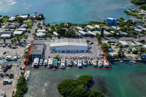 Tap into one of the fastest growing islands in the Florida Keys, with this investment opportunity located just outside the city of Key West. Over one acre with approximately 300 feet of waterfront, two metal frame buildings with approximately 19,700sf. Potential for dry boat marine storage operation and many other permitted uses under Commercial Mixed Use. Owner occupied with food market tenant and slips rentals. 15 live-a-board wet slips rented month to month.