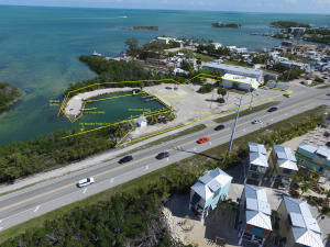 Listed $50,000 under appraised value. Rare opportunity to purchase the Historic 7 Mile Marina less than a mile from 7 Mile Bridge with over 360ft of US-1 frontage! Commercial property consists of protected marina, 3,600 sqft building. Marathon approved transferable building rights allowing 9,332 of commercial floor area, two tax keys totaling +/- 54,768 sqft or 1.25 acres. Property being sold ''AS IS'' no warranties or representations and no leases. Includes a deed restriction for neighboring property not to store straps within 75 ft of NE property line. Prior to 2014 fire, property had a 150 seat restaurant and office.