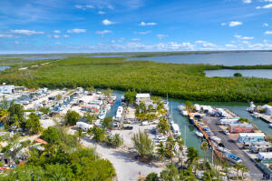 North Key Largo Marina!!! 754 Linear Feet Waterfront Dockage with direct Ocean Access. Live aboard slips and ten docks for Smaller Crafts 25ft under, 21 Dockside  power and water hook up pedestals with 30 and 50 amp. Communal showers, baths and coin operated laundry for live-boards.  Two apartments with amazing open water views: 1 bedroom and 1bath and 2 bedroom and 1 bath top floor unit.  Units are in process of being remodeled. Commercial space that was used in previous years as a restaurant/bar. Plenty of storage space. Large parking area. Individual Sewer Plant on site(2013).