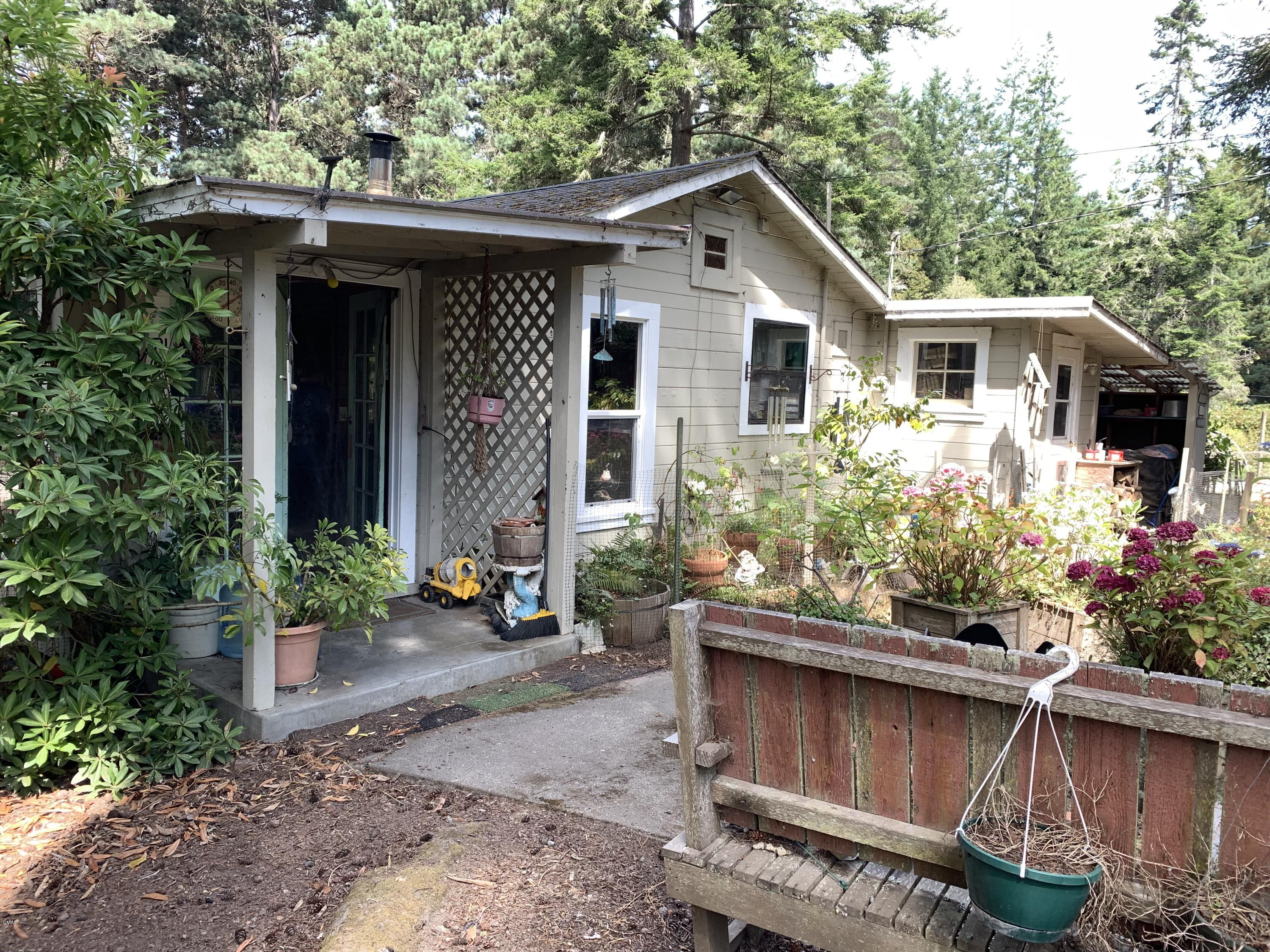 MUST SEE! 2.5 Acres with house for 400K!!! New Windows, new paint, new flooring,  the works. 2.5 lovely sunbelt acres, 1 cute house with 3 bedrooms- or 2 Bedrooms and an office (Two bedrooms have walk in closets)  AND 2 large detached shops, green house, huge chicken coop and more.  Lovely fenced garden areas, property extends down to Digger Creek. Walk to forested trails, close to town yet worlds away.