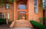 The welcoming front entrance with a custom teak wood and glass door.