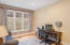 Formal living room is currently used as a home office and features a French door with transom and over-sized windows.
