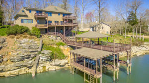 The oversized two-story boat dock has an upper level is partial covered and partially uncovered, boat lift, and two sea-doo lifts.