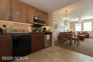 Galley kitchen with refrigerator, range, dishwasher, microwave oven, and sink