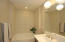 Master bedroom bath with tub , dual sinks and upgraded decorative lighting fixture.