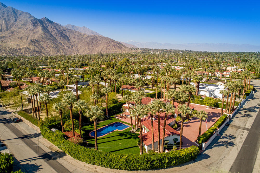 Welcome to this one of a kind, perfectly restored, romantic, 2-story Spanish Colonial on  approx. 1 acre of land situated in the coveted Palm Springs neighborhood of Old Las Palmas. Taken down to the studs in 2001 the property has been expanded with the acquisition of ½ adjoining lot and lovingly restored as a family compound for their personal use. No expense was spared, as can only be appreciated by viewing in person.  The home exemplifies the architectural style of earlier eras and has the distinct look of a WALLACE NEFF design.  The 5 bed/9 bath home offers approx. 6255 sq ft of living with 2 master suites & 3 guest suites plus a theater, upstairs sitting room and exercise room. The sparkling pool is saltwater and redesigned in ceramic blue tile with a tanning bed and built in spa. The views and the grounds are impeccable offering a fruit orchard and 56 palm trees.  Ideal for that car collector as there are 3 garages attached to the house and a free standing 2000 sf garage with & its own driveway designed to house a luxury RV or up to 6 cars & motorcycles. (Ideal conversion to artl music studio or guest house) First time on the market in some 20 years, it is a rare opportunity to own an exquisite estate that needs no work & priced below replacement. See Doc