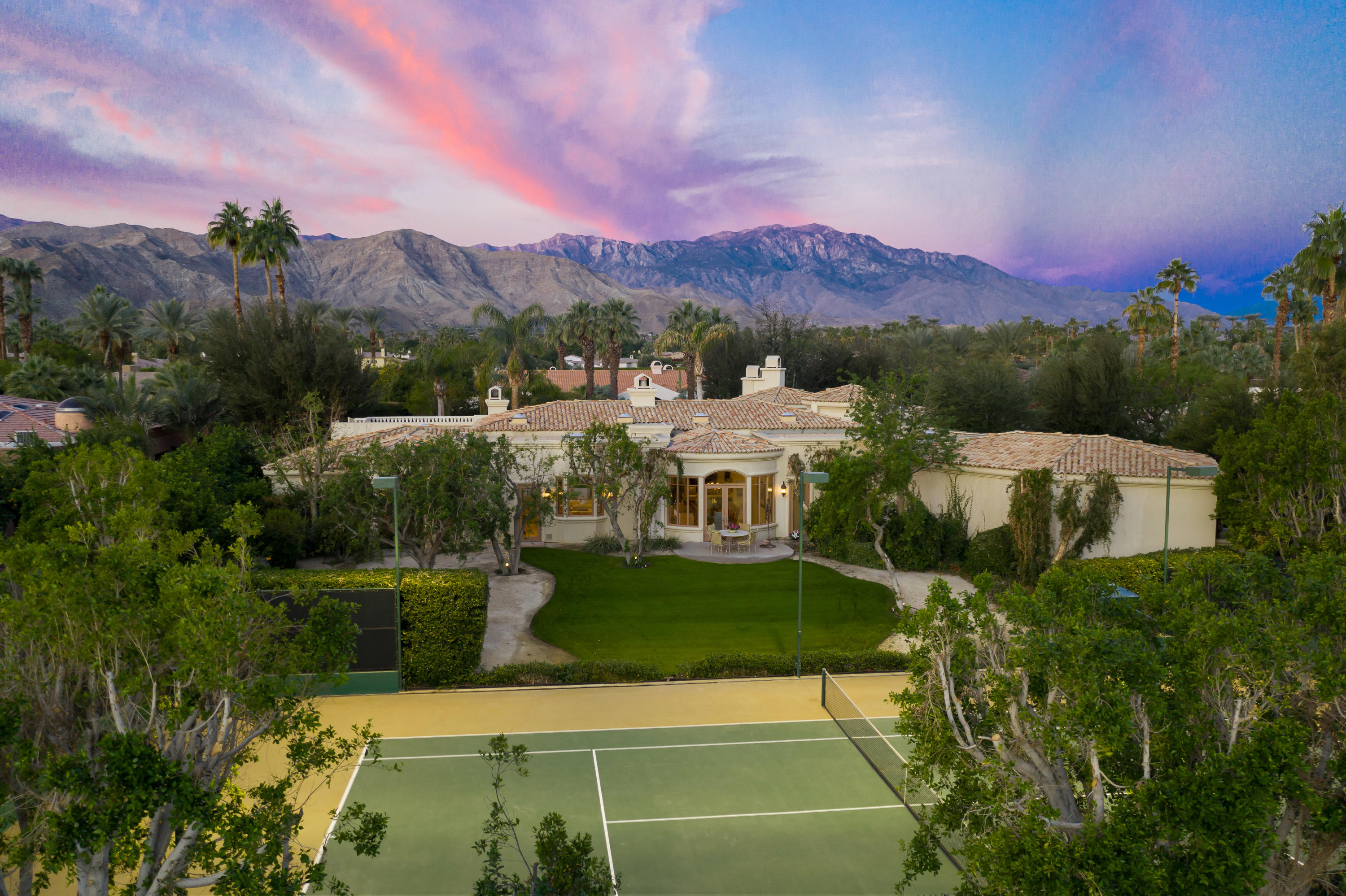 Gorgeous tennis estate at Mission Ranch in the heart of Rancho Mirage! Five bedrooms, five and a half baths plus gym and library. Approx. 5,783 sq. ft. on over one acre. Features two story entry foyer to formal living room with slab limestone wet bar and two way masonry fireplace that leads to family room and gourmet kitchen with granite counter tops, maple cabinetry, top of the line appliances and built-in desk area. Formal dining room, beautiful library with built-ins and fireplace, and a full gym or could be office.  Master suite with fireplace and inviting bath with custom glass block shower, jacuzzi tub, three vanities and his and hers walk in closets. Four more ensuite bedrooms make for perfect guest hospitality.  Exquisite finishes throughout including limestone flooring, cast limestone fireplace surrounds, coffered ceilings and more! The outdoor entertainment area features an extended veranda with fireplace and BBQ center. Custom salt water pool and spa with waterfall, lighted north/south regulation tennis court and roof top viewing deck.   The property features a wide variety of fruit trees and fantastic south mountain views! Mission Ranch is a wonderful equestrian neighborhood off prestigious Clancy Lane! Offered designer furnished per inventory!