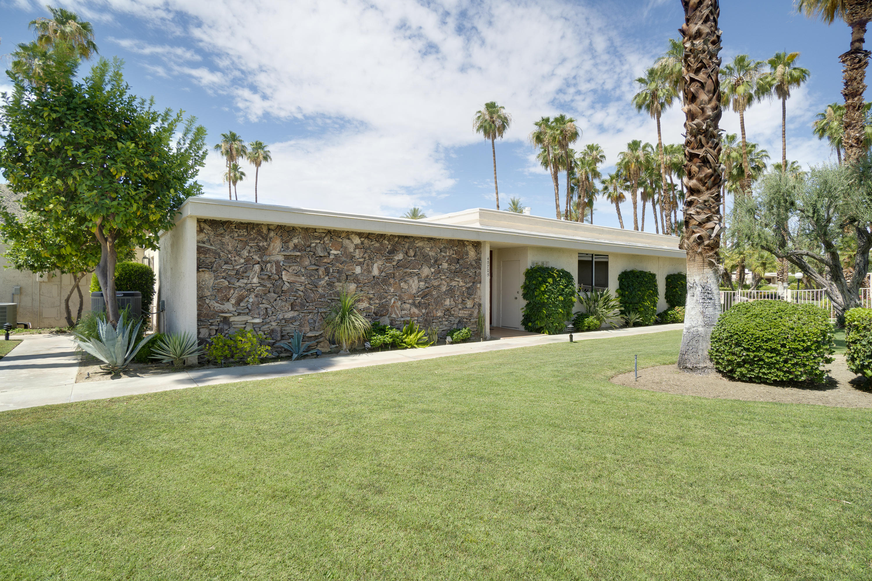 Rare Indian Wells Villa designed by architect William Krisel within the Indian Wells Country Club. This unique condo is a U shape surrounding an atrium that fills the home with light and provides an outdoor patio larger than most living rooms. Generous size rooms looking out to the mountains, large, meticulously maintained greenbelt area and community pool. The large living room is enhanced by a floor- to- ceiling rock fireplace; built-in entertainment center and wet bar. All bedrooms have ensuite baths; walk-in closets and open to an atrium or patio. The atrium is accessed through a beautiful, hand-crafted door. The garage is 2 car plus golf-cart space with ample storage. One New top of-the-line 25 Seer Lennox HVAC newly installed and second AC installed two years ago. Hospital grade HEPA Filtration system; New roof installed and warranty transfers; freshly painted throughout. New flooring in the entry; kitchen; powder room; master bath and hallway.  New carpeting in the bedrooms and living areas; new shower in the master bath; new cook-top and double oven; refrigerator; dishwasher and some new ceiling fans; new kitchen and master bath countertops by Artisan Design; new plumbing for toilets. Pride of ownership is evident throughout this fine home