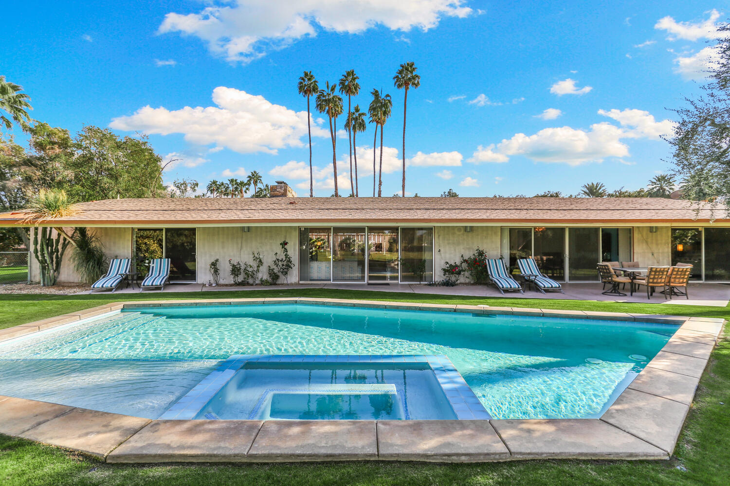 ..Award-Winning Mid Century Modern. Authentic time capsules like this beauty don't land on the market often. And when they do, they wind up selling in a flash. Ready for a new buyer to cherish this snazzy Atomic Age ranch built in 1958! Over the past half-decade, the property has been meticulously restored, & festooned w/ authentic furniture & accessories. Check out the terrazzo tile! Or those Sputnik lights! The geometric cutout screens! The shag carpeting! For fans of midcentury modern style, the photos are a feast for the eyes. The residence was originally designed by the renowned midcentury architect William F. Cody, & some of the original cabinets & bathrooms remain. It was remodeled in the 1980s, has since been restored to replicate the original decor. Even the orange, brown, & aqua color scheme was reinstated. The gorgeous restoration work earned the home a spot on the 2019 Signature Palm Springs Modernism Home Tour. The home also received a residential restoration preservation award in 2014 from the Palm Springs Modern Committee. The original sunken cocktail bar, described by the original owner, Sharon Simons, as 'the cat's pajamas,' is a true treat. And the chartreuse-upholstered bar stools flanking the space are scene stealers.The kitchen now boasts a more modern island w/ a sink, but the feature was designed to blend perfectly with the rest of the house. Other kitchen highlights include yellow & aqua tiles &  Danish Mod-style cabinets