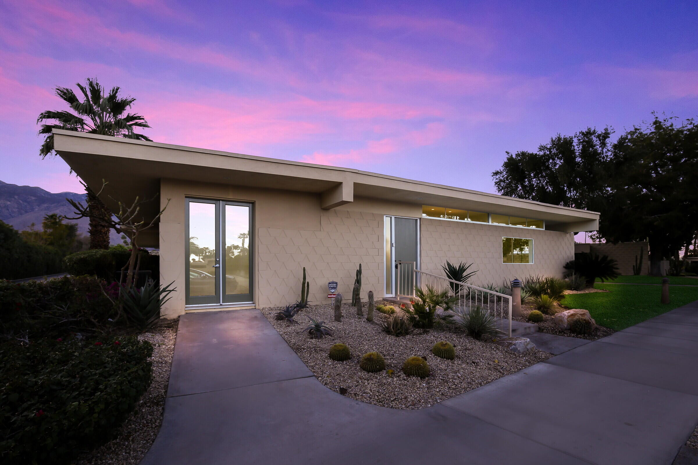 Completely remodeled to retain its Mid-Century Modern aesthetic while showcasing on-trend, high-style finishes, fixtures and appointments, this open and spacious condo presents a sublime opportunity in Palm Springs' guard-gated Seven Lakes Country Club. Generously proportioned at approx. 1,962 s.f. on one level, the chic residence is illuminated by period-perfect clerestory windows, floor-to-ceiling sliding-glass doors, and contemporary LED lighting fixtures. Sleek tile flooring, high ceilings and crisp white walls provide a canvas on which to imprint your preferred lifestyle. Entertain in a living room with corner fireplace that opens to the front yard via French doors, and enjoy indoor/outdoor living in a family, dining and kitchen area with access to a spacious covered patio. A playful modern accent wall adorns the family room, which flows easily to the dining room and a brand-new kitchen with quartz countertops, a long bar-height counter, gloss-white and wood cabinetry, and a full suite of stainless steel appliances. Two bedrooms and two fashionable baths include a primary suite with patio, mirrored wardrobe doors, illuminated vanity mirror, walk-in shower and dual sinks. Out of the line of fire yet only steps away from the fairways this home is conveniently located next to the community pool and parking area.  A must see at Seven Lakes Country Club.
