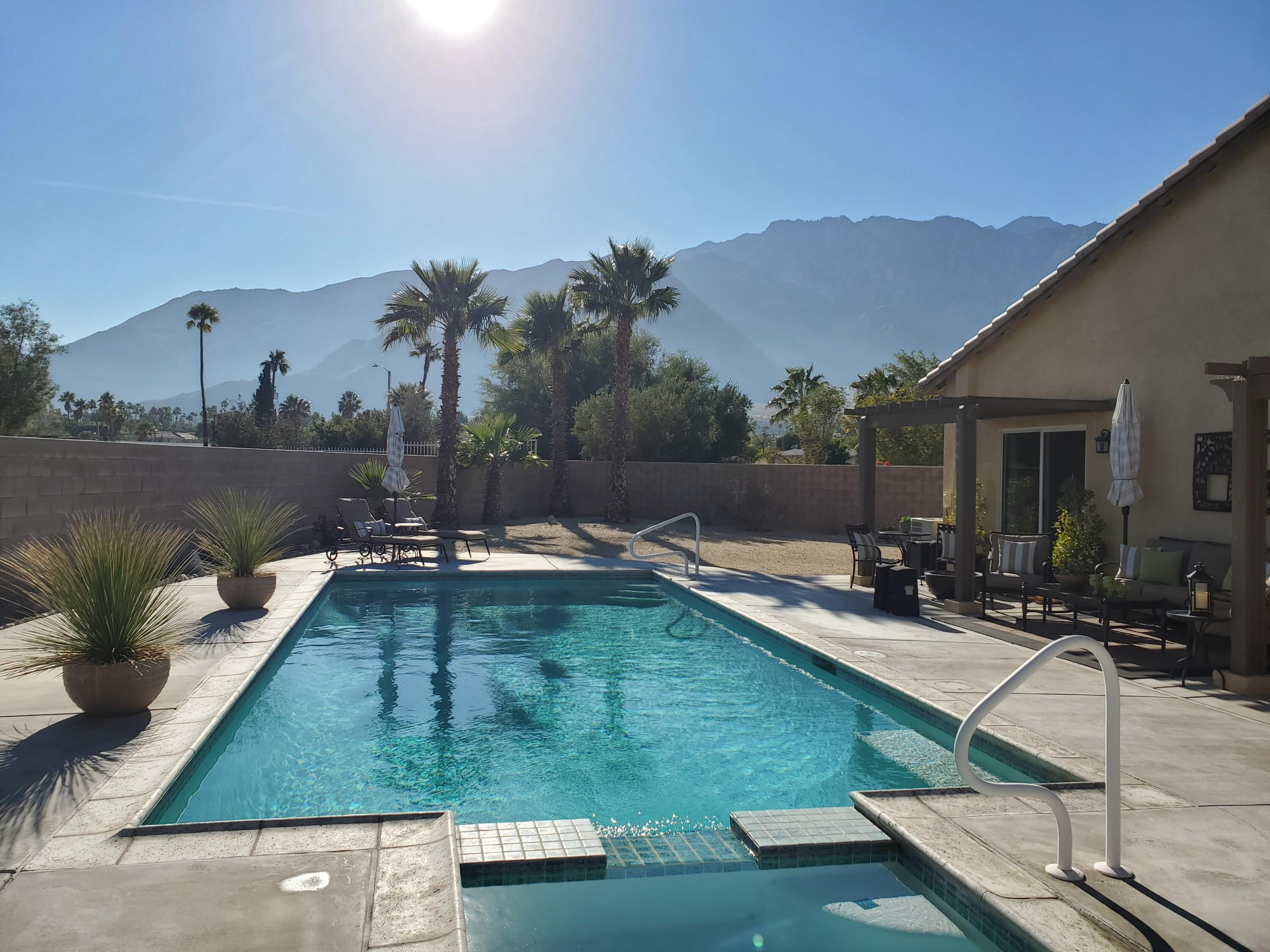 The picture says it all, classic Palm Springs, blue skies, sunshine and Palm Trees!   With that backyard view, you will feel like you are on vacation every day of your life!  This house has been well maintained inside and out.  Perfect vacation home or full time residence!  Large great room has cozy fireplace for those rare cool winter evenings.  Large island for cooking and counter seating.  Has Large pantry and inside laundry room.  Two car attached garage.  Wander outside to your private oasis with large pool and spa, spectacular views and nice outdoor seating or dining area.  This is also one of the rare smaller homes with private gated RV parking!  The community has community pools, spas, tennis courts, basketball court, BBQ / picnic area, playground, walking trails, and roving patrol. Super low HOA dues at 120/month.  You own the land!   Located just off Palm Canyon, a short drive to dining, shopping, entertainment and the Palm Springs Tram.