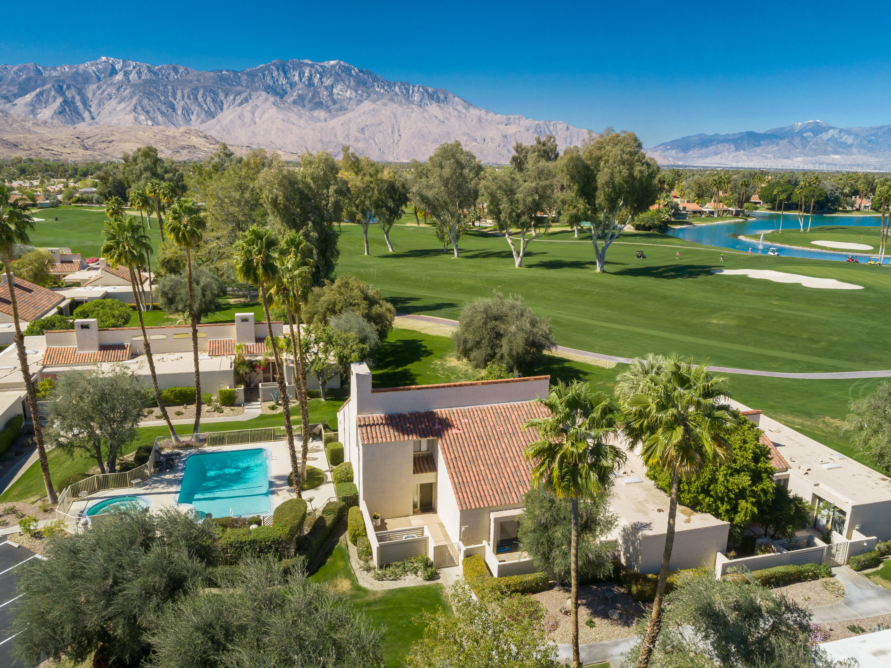 Exquisite Mission Hills Country Club condo with majestic panoramic golf and mountain vista views. This two-story residence boasts 2670sqft. of interior living space, including 2 master retreats, a loft/3rd bedroom, multiple balconies, and incredibly attractive voluminous wood-beamed ceilings throughout. The great room features a full wet bar (w/granite counter/backsplash), tile-encased fireplace, track lighting, plush carpet and large picture window bringing in ample natural light. Adjacent is the dining area, w/buffet counter/cabinets, and remodeled Chef's kitchen including stainless appliances, refaced cabinetry, newer wine fridge, recessed lighting, slab granite counters w/bullnose edging, island bar seating, washer/dryer cavity, custom gas range hood and built-in microwave. The downstairs master opens to the front courtyard, and en suite bath has dual vanity, w/brushed nickel faucets, all new sink valves, spacious tiled shower, separate tub and ample closet space. Both floors have newer HVAC units and upstairs includes the convenient loft/3rd bedroom and nearby upstairs master with shower over tub, dual vanity and balcony with excellent views. The community pool/spa is literally steps away. Fantastic proximity to the LPGA's ANA Inspiration event, golf's first major tournament of the year. Mission Hills C.C. is centrally located to the renowned Eisenhower Medical Center, world class restaurants and a plethora of golf courses! Make an appointment for a private tour today.