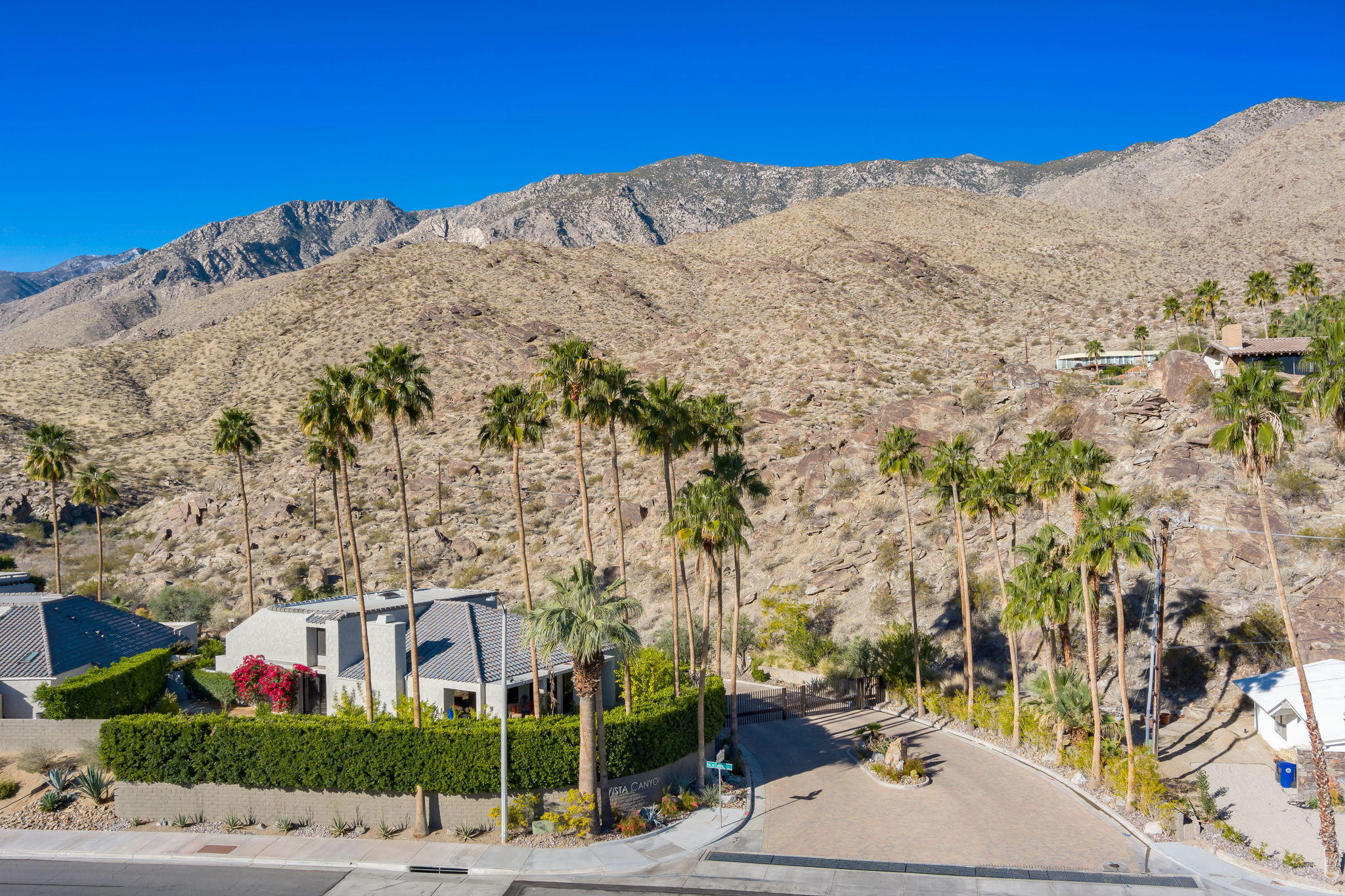 Rare opportunity to own in the highly sought after gated community of Vista Canyon in South Palm Springs. Theperfect location of this stunning home brings the outside in with panoramic south mountain views. This is truly desert living at its finest. The large open floor plan connects you to a dining area, living room, fireplace, wet bar, high ceilings with 3 skylights and a wall of glass, all looking out to the large patio withprivate pool, complete with custom swim up bar, and spa. A remote controlled awning provides the patio with shade from the afternoon sun. The2 master suites and third bedroom/office/den all have private outdoor patios. The upstairs master suite opens up to a deck, which offers amazing south/east mountain views. The bright kitchen, upgraded with new granite counters, is attached to a breakfast area that leads to a private patio. New HVAC unit installed in 2017 and warrantied till 2027. This home has ample storage including a 2 car garage with custom storage cabinets and flooring. The laundry room is equipped new washer and dryer. This complex is gated on land you own (fee simple). There are only 29 homes, 2 pools and spas, and a full size tennis court. Vista Canyons is close to hiking trails, golf, world class shopping and 5 minutes drive to  downtown Palm Springs. The beauty of this complex is accented by the magnificent desert landscape and new paver tiles throughout the complex.