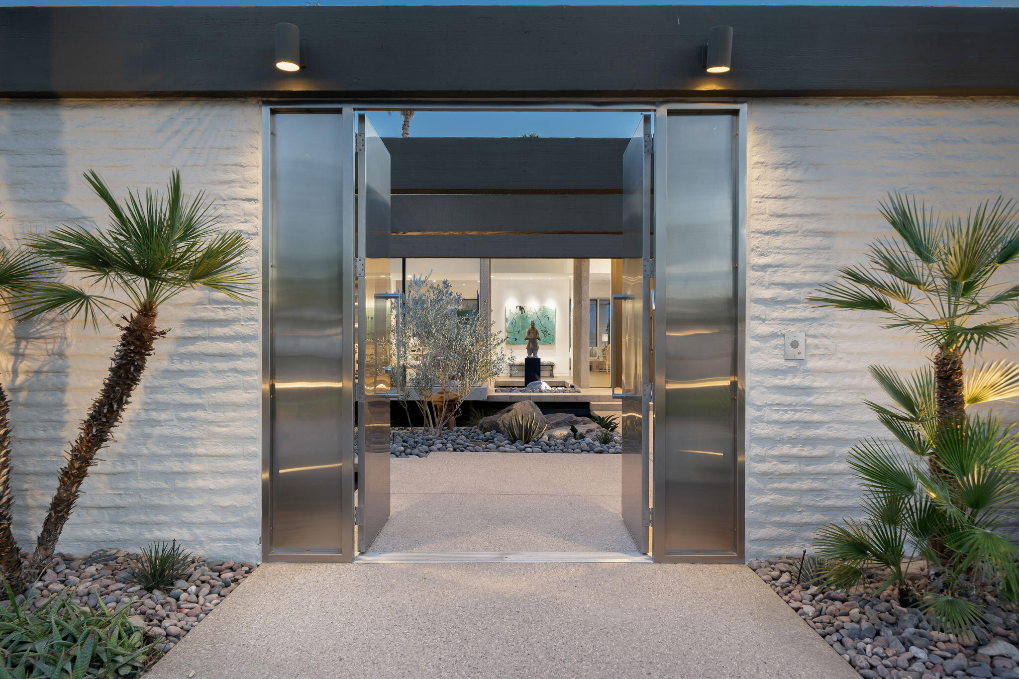 The stainless steel double door entry reveals a private courtyard with a stunning water feature. This custom desert contemporary home has it all, soaring ceilings, walls of glass, magnificent mountain and fairway views, large walls perfect for art collectors and total indoor outdoor living. The backyard is complete with covered patio, outdoor dining area , barbecue, sculpture and pebble tec pool and spa. Living room has wood flooring, sunken remodeled bar and fireplace,  The entertainers dream kitchen includes granite, stainless appliances, large island, walk in pantry and breakfast room. The large primary suite offers a sitting area, dual bathrooms and walk in closets. Invisible ceiling speakers installed in primary bedroom, living room, dining room, & den! The den cantilevers over the water feature, an office, two en suite bedrooms, exquisite powder bath and laundry room complete this exceptional home.