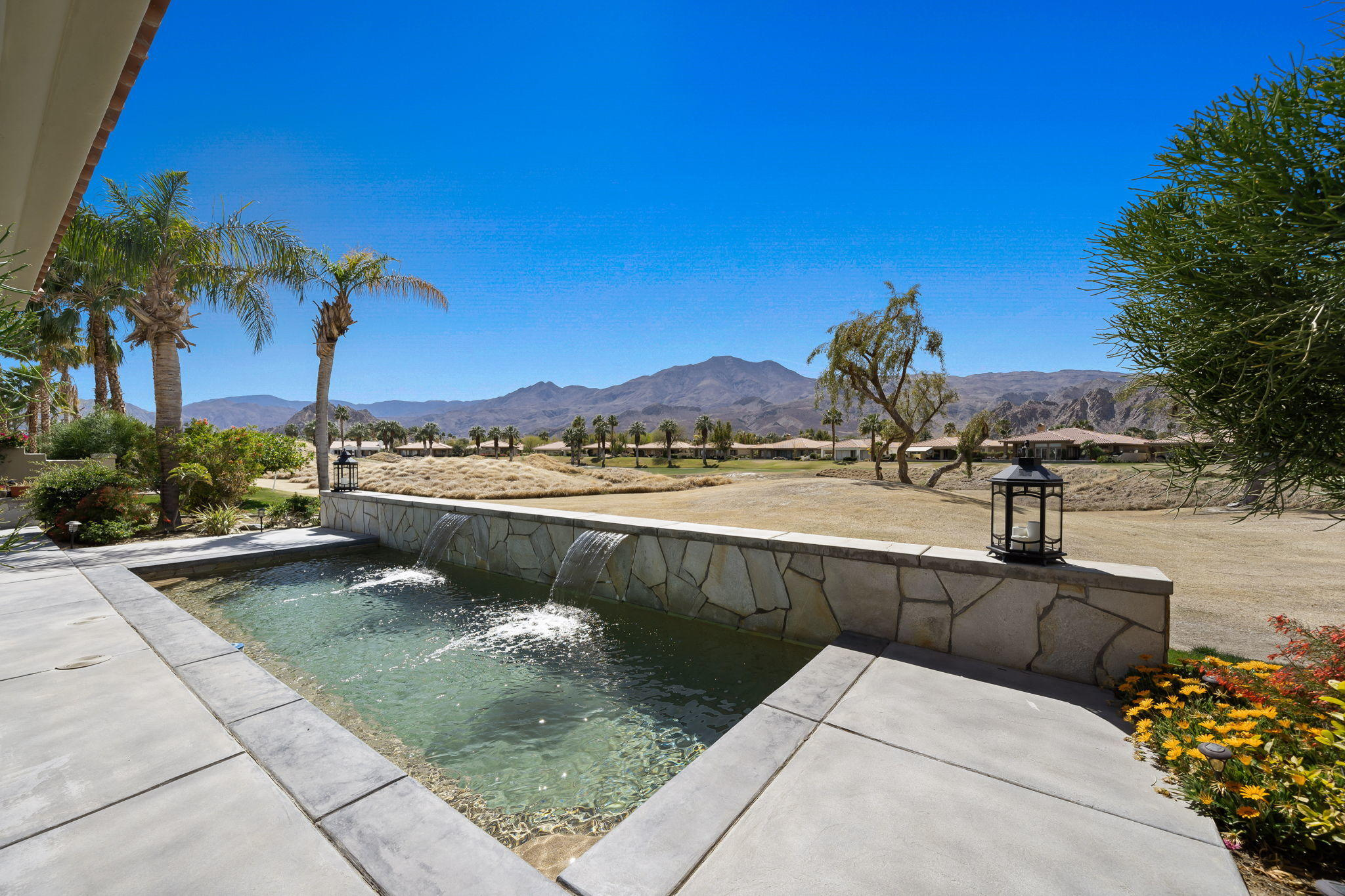 Located behind the private gates at PGA West sits this popular Heritage Three plan with detached Casita! Incredible Southwest facing views of the Santa Rosa Mountains & 11th fairway of the Nicklaus Private course! This home is impeccably maintained by these owners!   Since purchased they have added a Pebble Tec Pool, Rock, Fire Pit, Water Heaters, Sub Zero Refrigerator, 2 Boesch Ovens, replaced 2 of the 3 AC units and installed Epoxy floors in the garage!  Private courtyard entry leads into the foyer with tile flooring, double sided fireplace that separates the living & family room, & wet bar! The Culinary kitchen has ample counter space, soft white cabinetry, granite slab counters, double ovens, gas cook top,  pantry & kitchen nook with picture windows looking out to the view! Master suite offers your own private retreat with large master bath with soaking tub, walk in shower, double vanities & walk in closet! Your visitors will love the guest rooms both with there own en-suites or a stay in the detached Casita for the ultimate privacy! This home has it all! A Must See! Offered furnished!