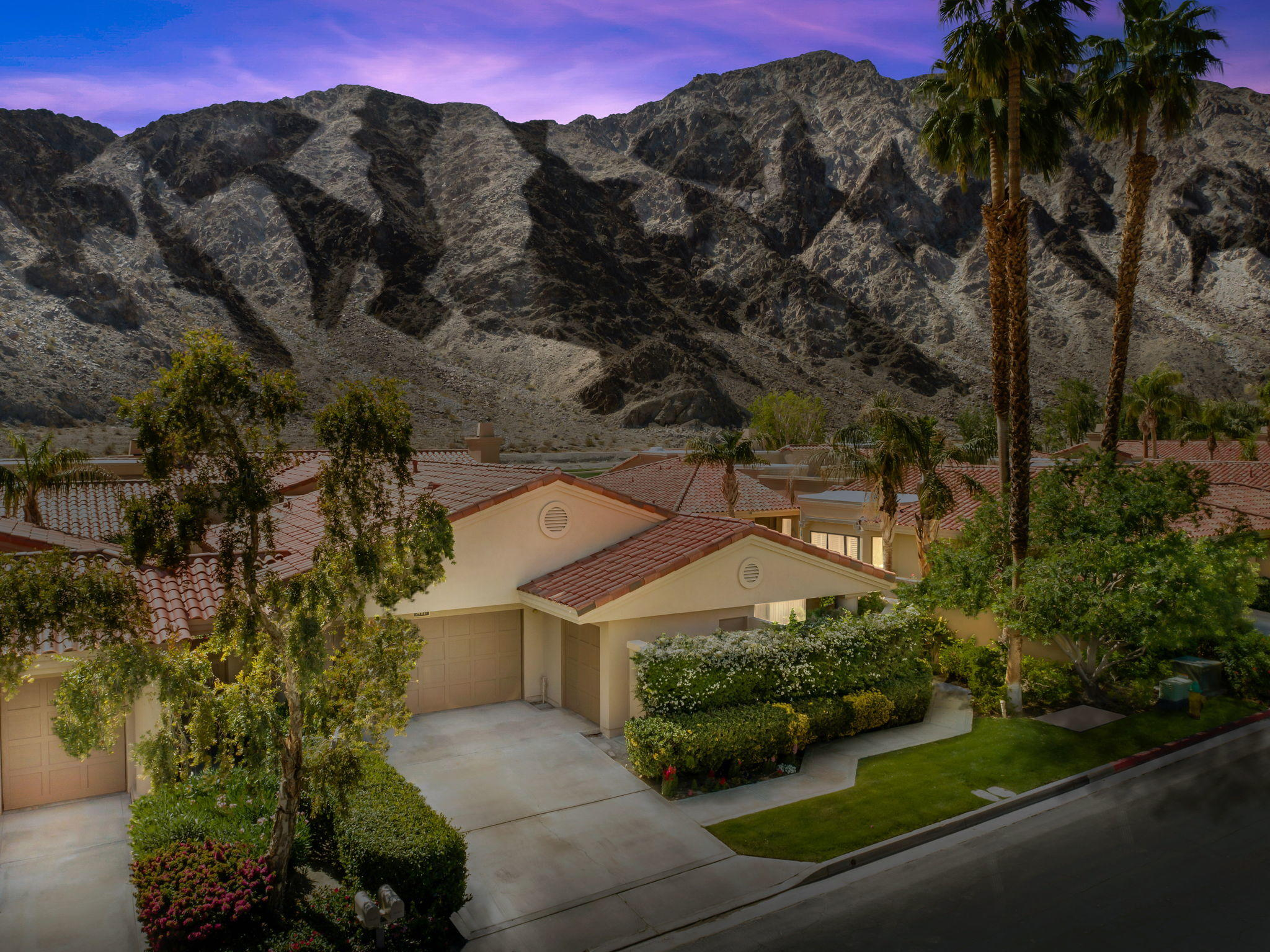 Located on the 14th hole of the Palmer course at PGA WEST with unobstructed western mountain and golf views. This location is a 10+. Watch the golfers and the bighorn sheep from your back patio and at nighttime the mountains light up.  Lots of opportunity from this legends 40 3 bed/3.5 bath condo 3031 sq ft.  Great entertaining home.  Expansive living space with kitchen open to family room and views.  Large living room/game room including sunken wet bar with vaulted ceilings and dining room opens to the views and sunshine.  All bedrooms are large with bathrooms in suite.  Attached two car garage with direct access to the home make this a popular floor plan. Extra golf cart garage for cart or storage.   Community pool and spa located very close by.  These locations do not come on the market very often.  HOA includes exterior landscape maintenance, exterior property maintenance (paint, roof, insurance), Cable tv/internet, trash, community pools/spas and community patrol/security.  Come enjoy the desert resort lifestyle!