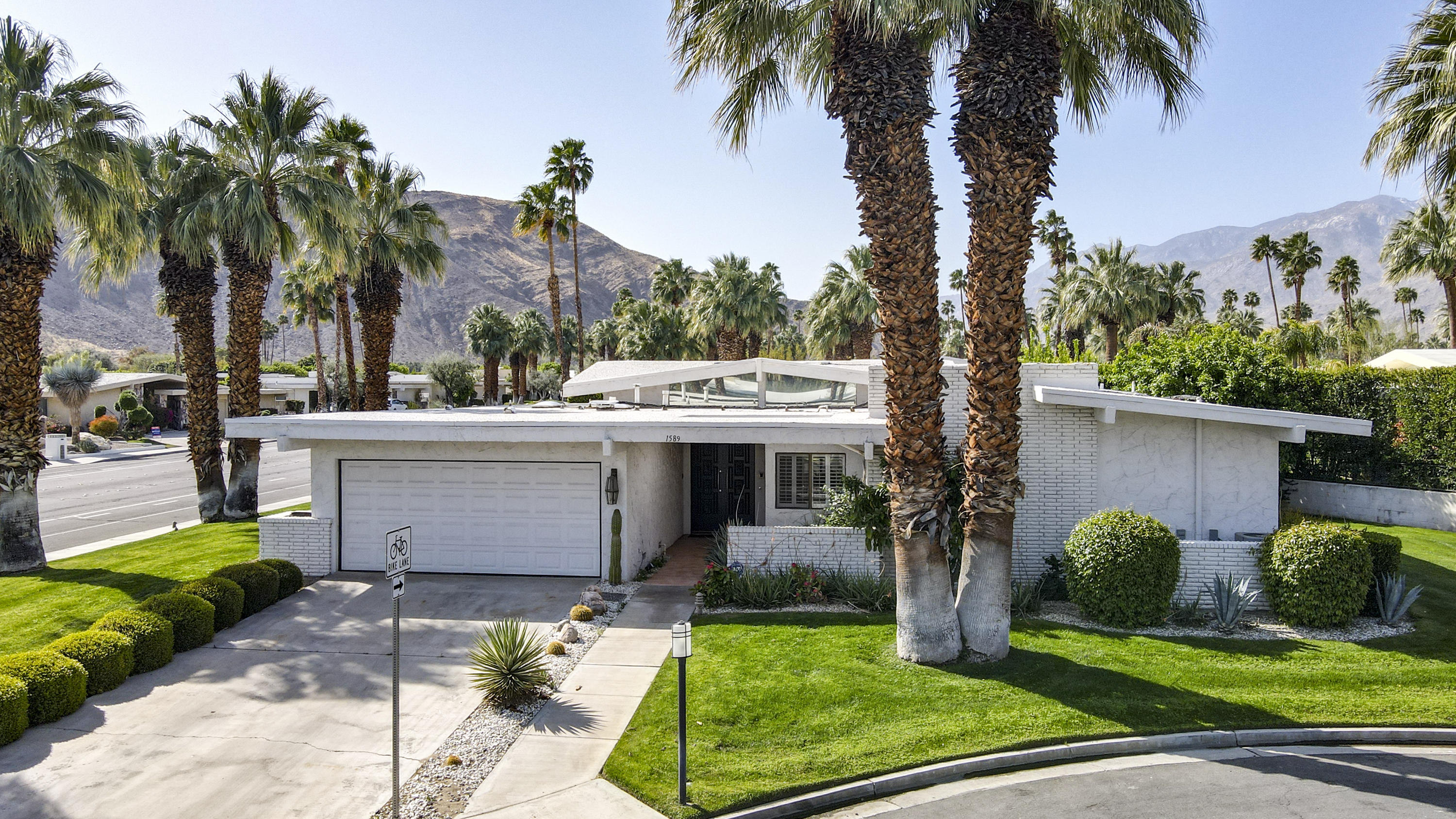 Freestanding and detached Canyon Estates Mid-Century style residence designed by Architect Charles E. Dubois in South Palm Springs. This 3 bed/ 2.5 bath home has been well maintained and is mostly in original condition. Some of the iconic features of his design are expertly represented in this home- clean, simple lines, high ceilings with clerestory windows, open floor plan and ample windows bringing the outdoors in. The living/dining area has high, vaulted ceilings and the classic Palm Springs wet bar. The kitchen features a breakfast area, skylight and interior laundry area. With two large ensuite master bedrooms, one with direct access to the covered patio, both have walk-in closets, updated bathrooms with separate shower & tub and dual sinks. A third bedroom is possible, but currently used as a family/media room with gas/ wood burning fireplace. The property is complete with a large corner location, on a cul-de sac and has a private patio with numerous up lit fruit trees and mountain views.  Canyon Estates has 15 pools, 12 spas, tennis courts, a 9-hole executive golf course, and renovated clubhouse with gym/weight rooms. Long term, reasonable land lease through 2063