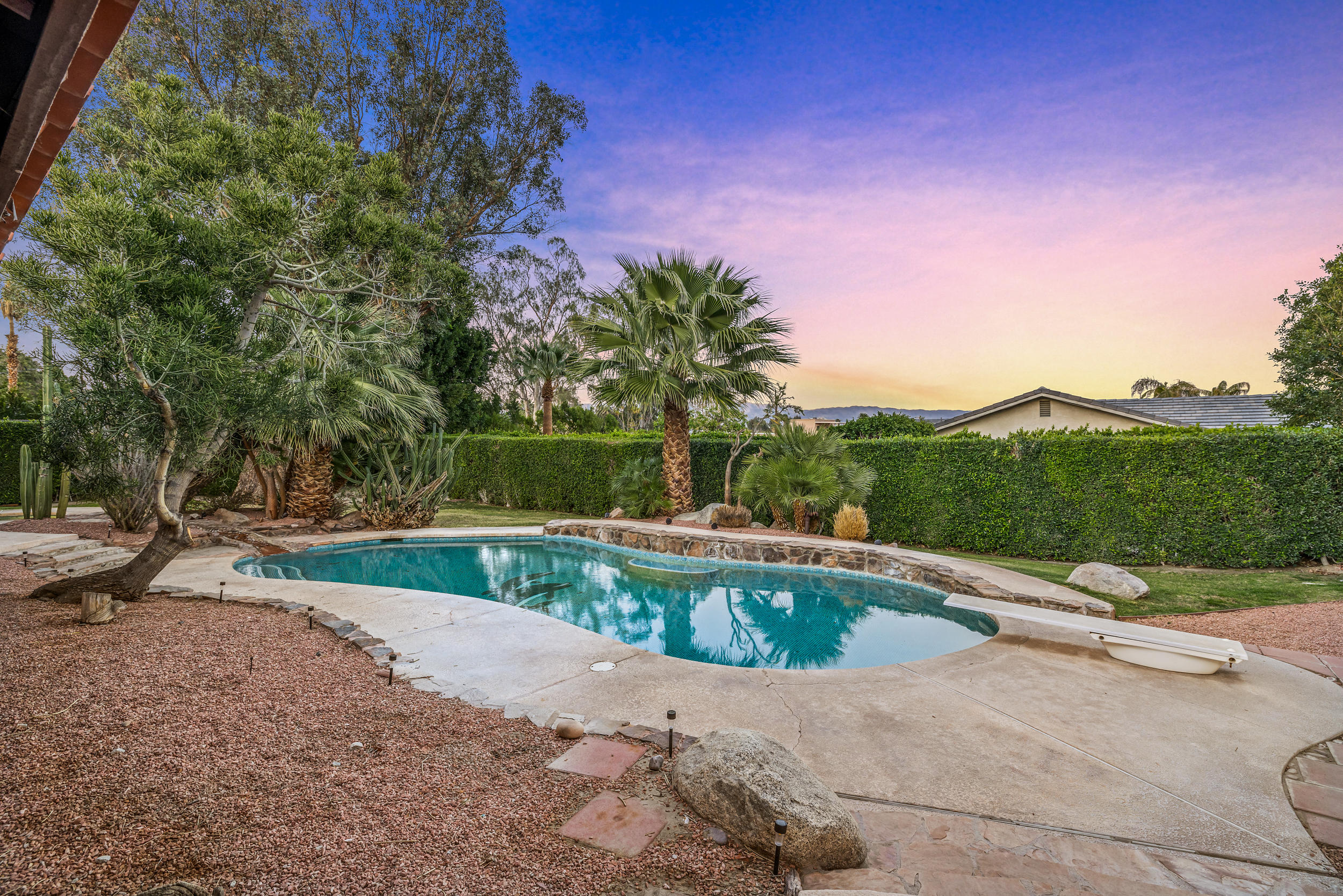 Unique opportunity to own this one of a kind property located in east Palm Desert. This home has 3,121 square feet of living space and sits on over half an acre corner lot w/an amazing private detached 30'x 50' RV garage with a two post hydraulic lift. In addition to the RV garage, there is a traditional two car garage both are equipped with evaporative coolers which have been replaced in the past 2 and 3 years. There is also owned solar and windows, doors and sliders have been replaced. This is your opportunity to make this three bedroom, plus bonus room, which can be used as a fourth bedroom or office, 3 bathrooms, living room, formal dining room and bar area, fireplace, kitchen with breakfast room, into your desert oasis. This home has 18' x 18' tile throughout with exception of the master bedroom, plus plank tile in the living room. You will love the backyard with a beautiful pool, spa and creek that runs from the spa into the pool, there is an enclosed covered patio, mature landscaping and some sweet mountain views. The circular driveway is great for additional vehicles, plus not to mention the additional parking area behind the gated fence. Lots and lots of room for your car collection, boats, SUV's, sport utility vehicles, motorcycles or motor home. The possibilities are endless. There are no HOA fees, Mello Roos or land lease here. Contact the City of Palm Desert for Onsite Owner STR opportunities.