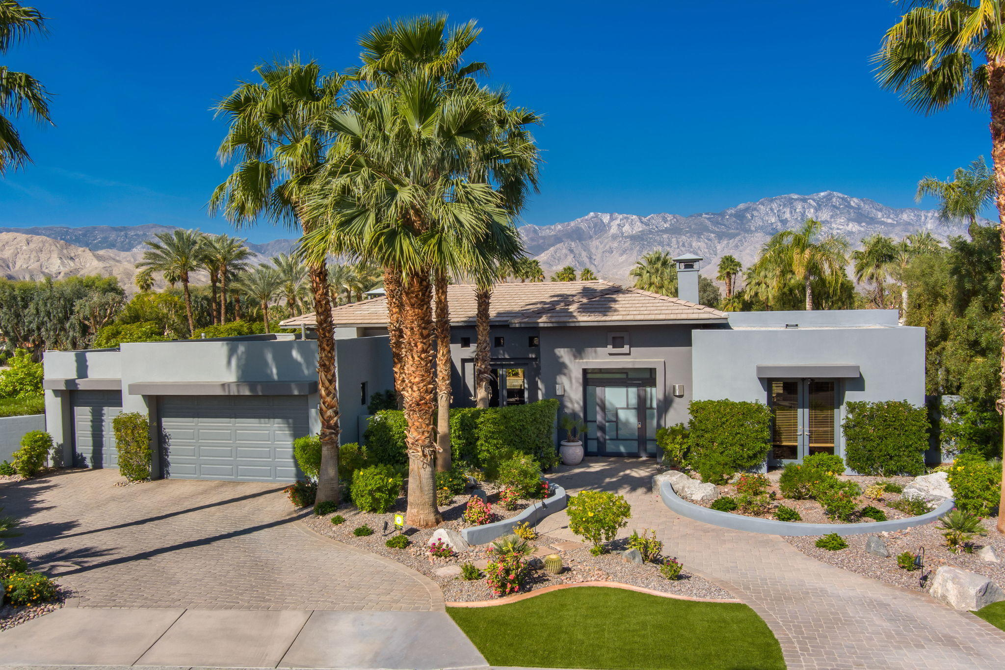 Amazing Contemporary with South and West Mountain Views on Resort Sized Lot.  Open Great Room Floor Plan and Outdoor Living Room in Coveted Artisan.   Great curb appeal with contemporary architecture and custom desert landscaping.  Enter through  contemporary gates to an outdoor entry hall with fountain.  Inside is an Open Great Room with book matched granite fireplace, built-in entertainment center, walls of glass with multiple sliders to outdoor living and stunning mountain views.   Gourmet Social Kitchen features granite countertops and stainless appliances with counter seating and views. Dining area with custom lighting and French doors.  Master Suite with custom built-ins, mountain views, French doors to the terrace and a spa bath with marble finishes.  2 guest suites each with ensuite bath with travertine finishes provide great space for friends and family or an optional office.  Outside is a true resort on an oversized lot with Covered Outdoor Living Room featuring a fireplace, TV, Built-in BBQ and Misters..   Resort Pool and Spa with waterfall and a putting green surrounded by citrus orchard all with great south and west views and sun.  Large lot provides opportunity to add a casita if desired.  Solar equipped, electric shades, updated lighting and even a garage AC - this property has it all.   Come home to your own private contemporary desert retreat!