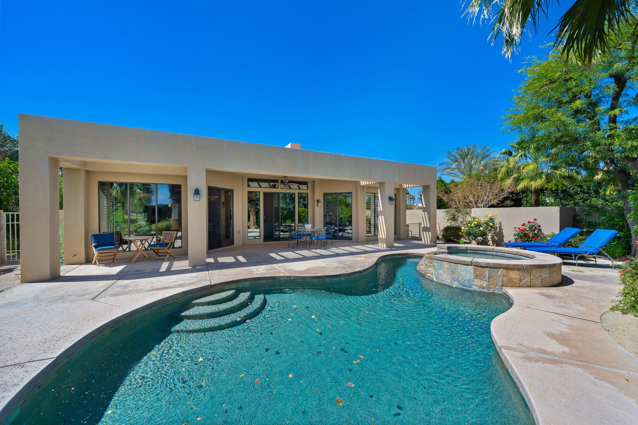 Contemporary with Open Great Room Floor Plan and Multiple Private Outdoor Spaces.  Corner Lot with  Side Drive and Beautiful Palms at Entry.  Enter through a gated south facing courtyard with fountain, outdoor living space and custom landscaping.   Entry Hall Tower makes for dramatic entrance to an Open Great Room with Stacked Stone Fireplace, Entertainer's Bar, Dining and Walls of Glass opening to the Pool Terrace making for a light and bright home. Gourmet Kitchen with Stainless Appliances including Thermador Cooktop and Ovens, breakfast bar open to Great Room and a Morning Room with french doors to the courtyard. Master Suite features a stacked stone fireplace, retreat area, sliders to the pool terrace, a marble filled spa bath and double walk-in closets. A guest bedroom with ensuite bath and an office/bedroom in the house and a Casita with stacked stone fireplace and refreshment center provide great space for family and friends or office/gym space. Outside is an expansive and private backyard with pool/spa,  and covered outdoor living room.  Solar equipped with owned solar and updated flooring.    Come home to your Desert Retreat!