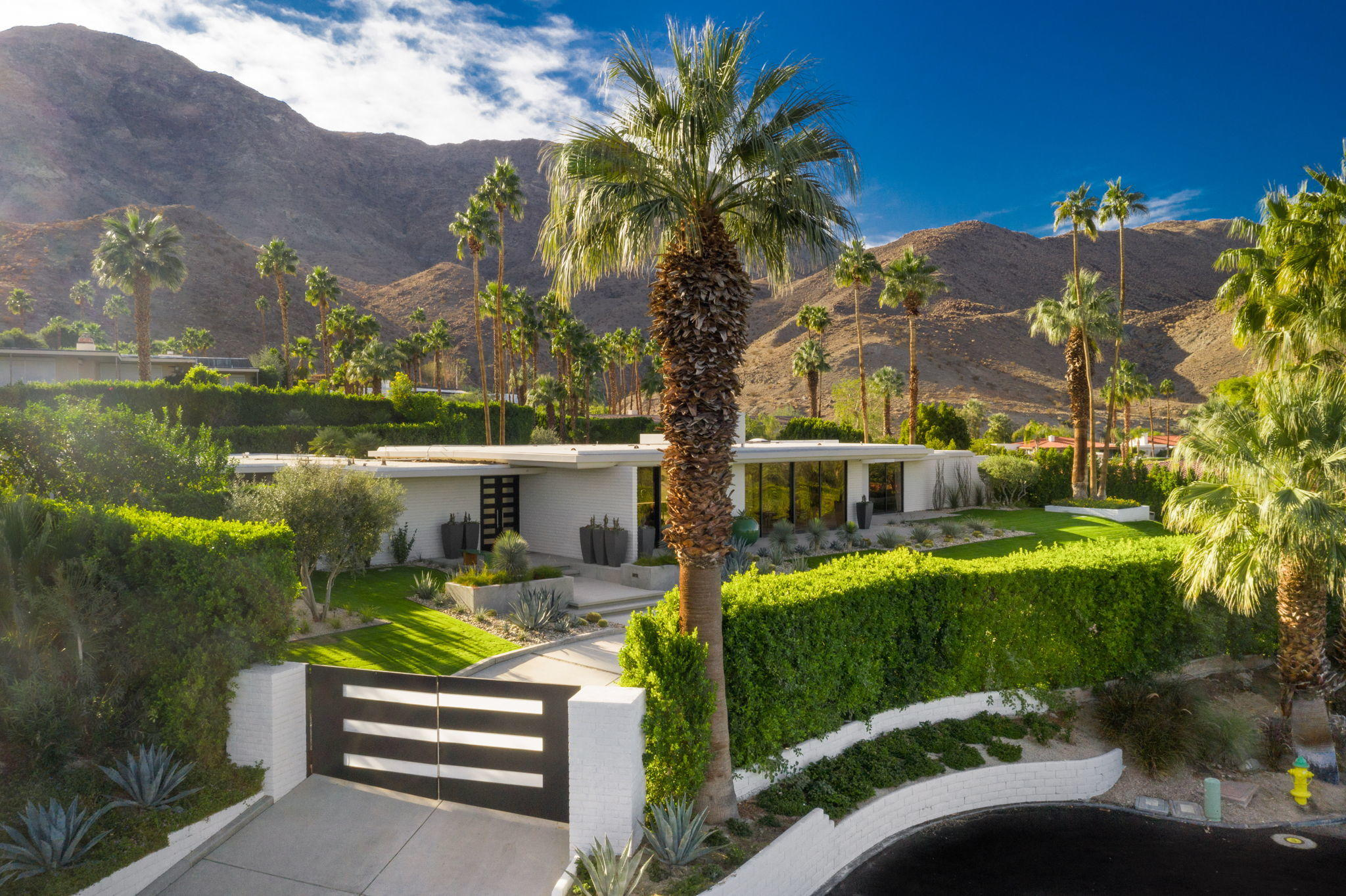 Exceptional modern estate located high above the desert floor in the  desirable gated community of Thunderbird Heights; offering 360 degree views. This sleek and understated luxury home boasts steal beam construction with slump stone walls iconic of architects William Cody and Donald Wexler. Attention to detail in design and function provide a Zen environment and evoke peaceful living while in perfect harmony with the desert lifestyle, Entertain your guests in an open great room with walls of glass bringing the outdoors in and providing a panoramic vista of the mountains,, outdoor lush landscape and the city lights below.4 bedroom suites , separate office , 4.5 baths with approx 4700 sqft of living space. The home has been meticulously renovated with attention to detail in the custom luxury materials and finishes used to compliment the  architectural design and linear details of  the space . The home is offered designer furnished with exquisite custom European Mid Century modern furniture. Exclusion list to be provided.