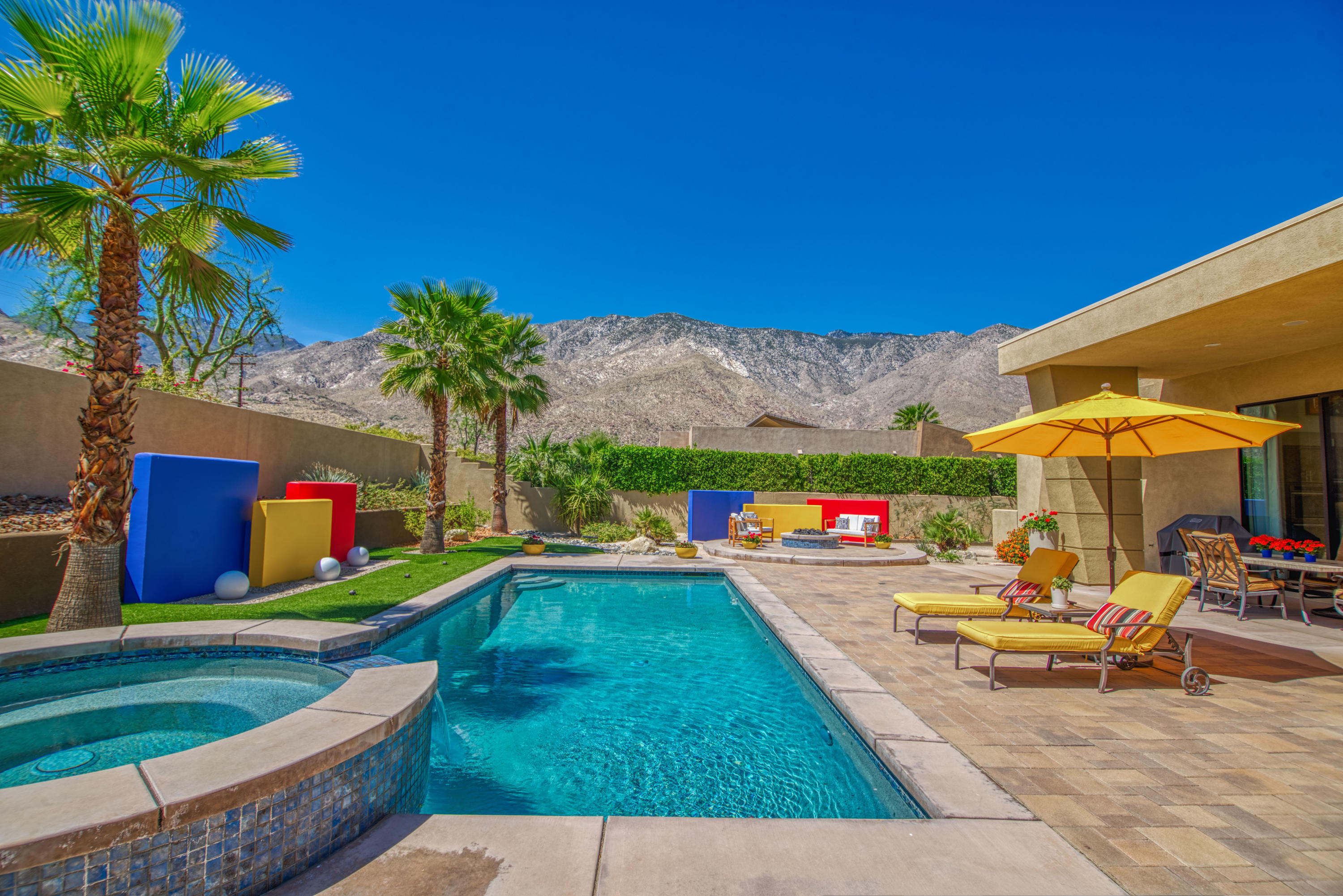 WOW!  High ceilings, open floor plan, designer upgrades and a south-facing backyard that features a resort-style pool and spa, outdoor architectural highlights inspired by Luis Barragan, custom lighting, professionally-installed artificial turf, gas firepit, and panoramic mountain views!  Welcome to luxury at Alta in South Palm Springs!  Private front courtyard with views leads to the expansive great room that has 14 foot high ceilings, clerestory windows, and three sliding glass doors that open to the south-facing backyard.  Spacious kitchen was upgraded with an extended island and includes a suite of built-in stainless steel appliances, a walk-in pantry, attached one car garage as well as an adjacent laundry room with sink that leads to the attached two car garage.  The large dining area with bar serves as an alternative work station and the living room styled up with an included 75'wall-mounted TV and 5 built-in surround sound speakers sets the scene for entertaining.  Adjacent family room also offers mountain views and a sliding glass door that opens to the backyard.  Master Suite offers high ceilings, incredible views, an included 65' wall-mounted TV, a walk-in closet and a private bath with dual vanities, a walk-in shower, and a separate tub.  Junior Ensuite Two also offers mountain views, a walk-in closet and a private bath with dual sinks and a walk-in shower.  Junior Ensuite Three has a walk-in closet and a private with a shower/tub.  Pre-paid solar lease, too!