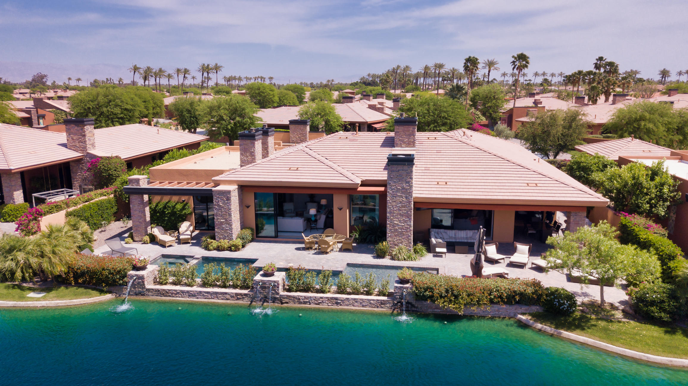 This unique luxurious Ironwood gem is move-in ready! Largest model in 24 hour live gated community with views of lakes and mountains!  Remodeled with  custom artisian wood floor planks.  Goumet kitchen includes Wolf stove top with grill, Wolf microwave with Sub Zero refrigerator, built-in wall ovens.  Two drawer below counter refrigeration, trash compactor all hidden under gorgeous granite counter. Built-in seating area off the kitchen. Niles surround sound throughout, google lighting controls, alarm system and more. The wet bar with 2 pour kegarator, ice maker, Perlick refrigeration will begin the party. Step outside from the Master bedroom into the spa and swimming pool.  5 custom fireplaces in this home. Fireplace in master & outside. Master bath includes marble shower and floors, steam in shower, jet tub, TV insert in mirror. Operation for controls of the house in master as well. Dining room & additional bedrooms tastefully decorated with same type decor. Casita has its own 2 sided fireplace, microwave, ice maker, refrigerator/freezer, & TV. Enjoy barbecuing on your built-in stainless steel BBQ with bar sink. Bask in the salt water swimming pool/spa with waterfalls while watching the game on outside TV. Airconditioning in garage and golf cart garage with finished floor and extra cabinetry. This show stopper home is located among lakes and hand trimmed gardens. Complete resort luxury living! Furnishings offered outside of escrow if interested.