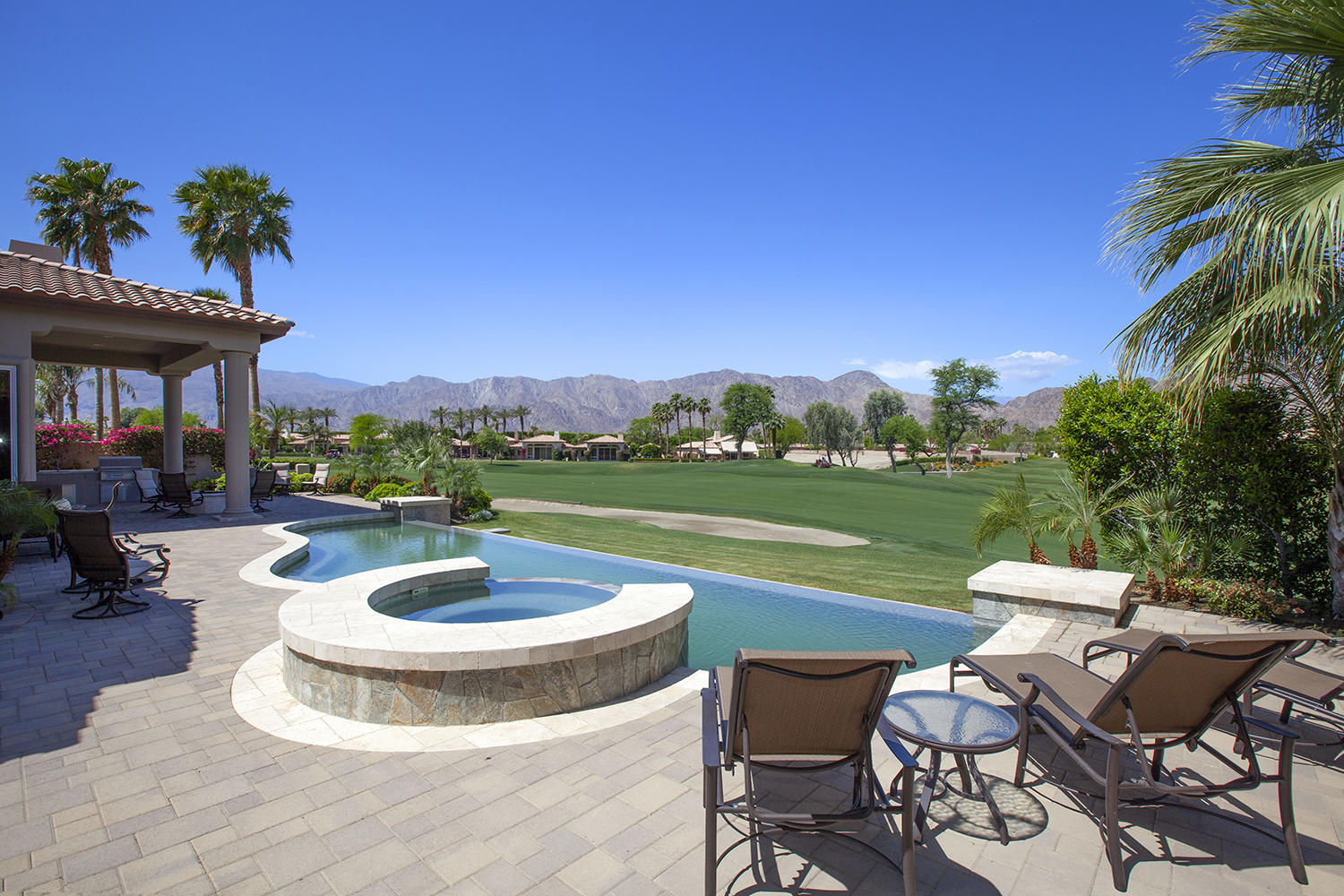 A Montana III unlike any other in Rancho La Quinta! Set on a near end of cul-de-sac estate lot, this home was rebuilt and re-envisioned in 2015 removing the primary wall that separates the formal living room from the kitchen & family room - resulting in a spacious greatroom configuration with views across the infinity edge pool, 14th fairway Jones Course & panoramic west Santa Rosa Mountains. From the marble flooring, to the completely reformatted kitchen with 2 floating granite islands, to the newer Fleetwood slider doors, York AC & even the roof, this home & floorplan have been refined and re-designed to create the ultimate Rancho La Quinta Estate. Private courtyard entry with custom glass and wood double door entry; chef's kitchen with newer granite surfaces, newer cabinets, backsplash and stainless steel appliances; electronic drop down blinds in great rm.; granite countered serving area with wine fridge & storage; all newer can lighting & custom linear fireplace; all newer raised panel solid core doors; newer interior baths with newer cabinets, counters and raised counter heights and newer hardware; infinity edge pool with extensive use of custom pavers and firepit; side loaded rear guest house sits in rear of property with bocce ball court and custom synthetic turf putting green and newer custom landscaping; 3 car garage and Water Cop flood detection system. Huge stainless steel & granite BBQ station; Furnished per inventory.